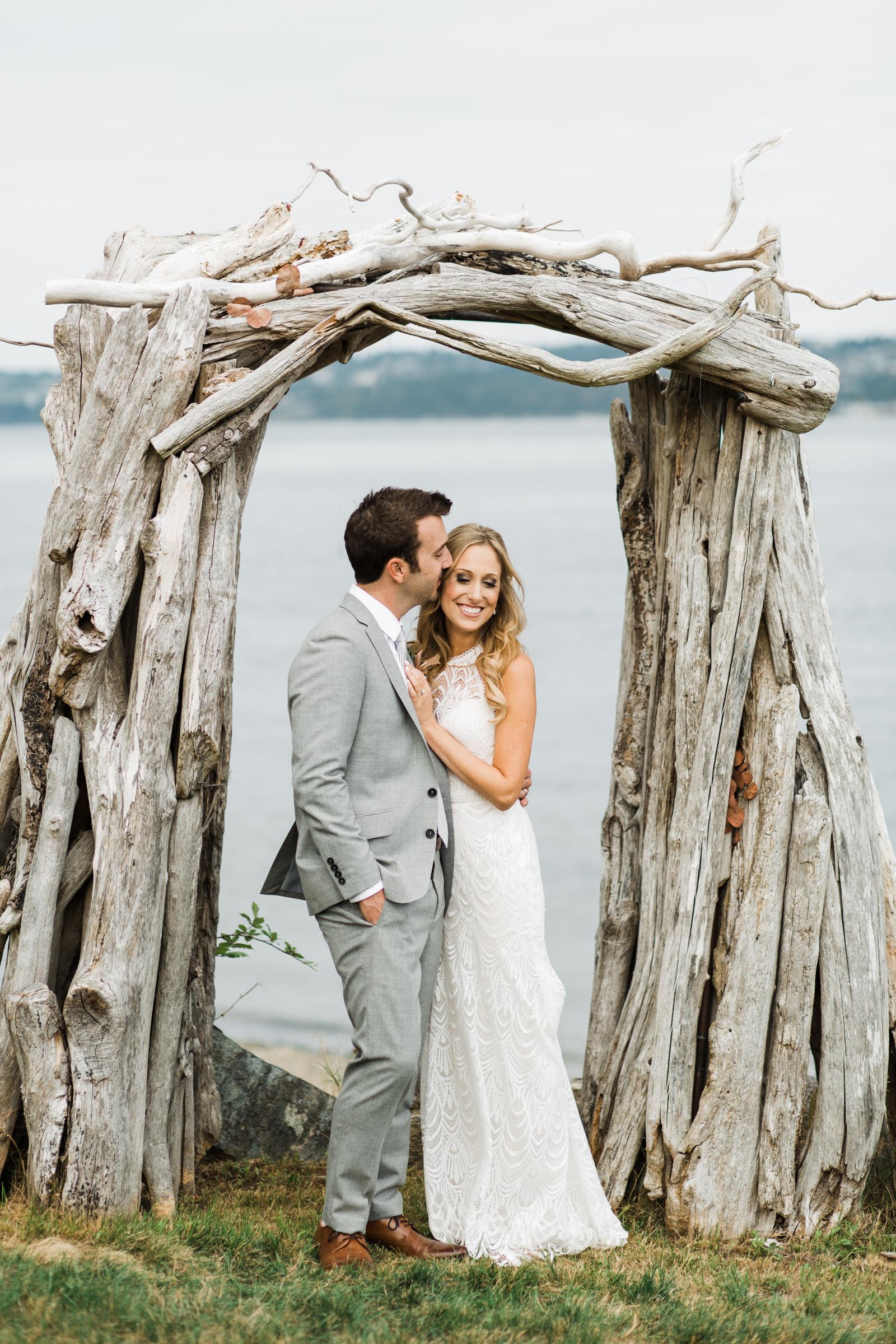 Couple cuddling under driftwood arbor - photo by Stephanie Cristalli Photography