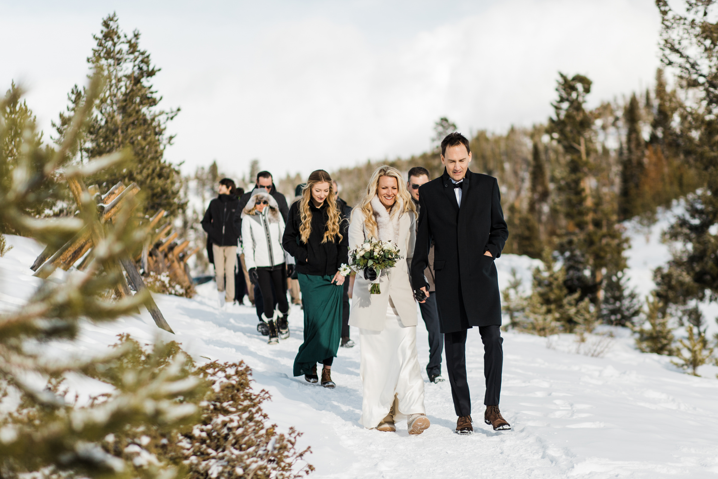 Couple makes their way to ceremony in the snow - photo by Stephanie Cristalli Photography