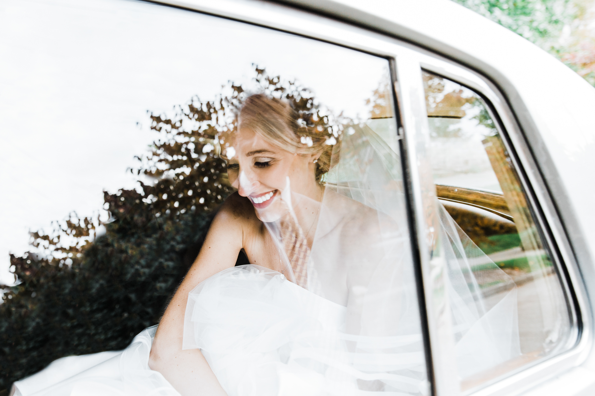 Happy bride wearing tulle in back of white limousine - photo by Stephanie Cristalli Photography