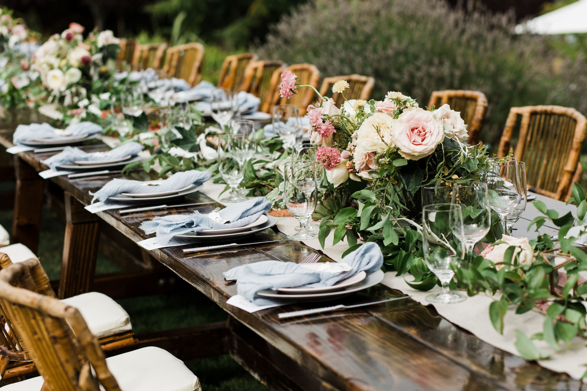 Wooden reception table with rustic cane chairs - photo by Stephanie Cristalli Photography