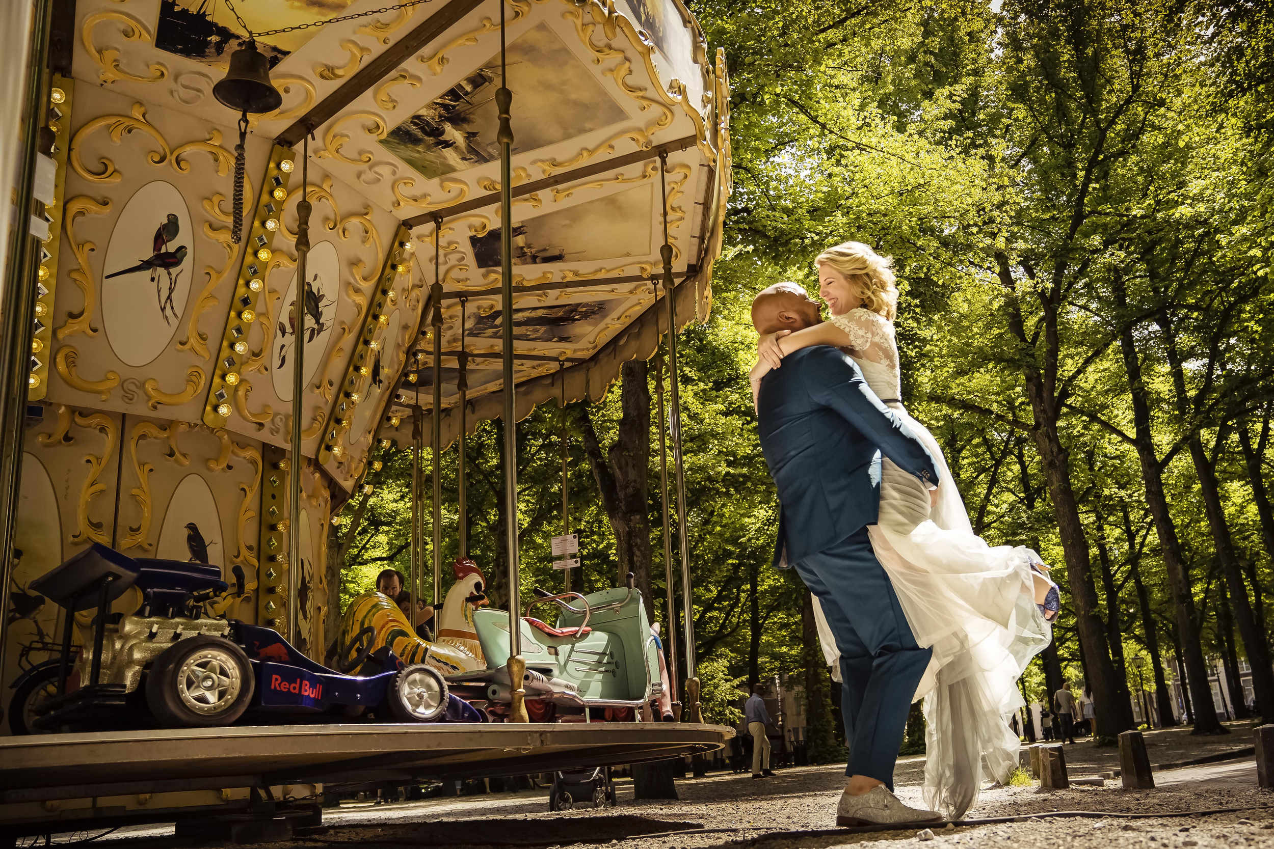 Groom lifts bride at carousel - photo by Studio Damon Photograpy