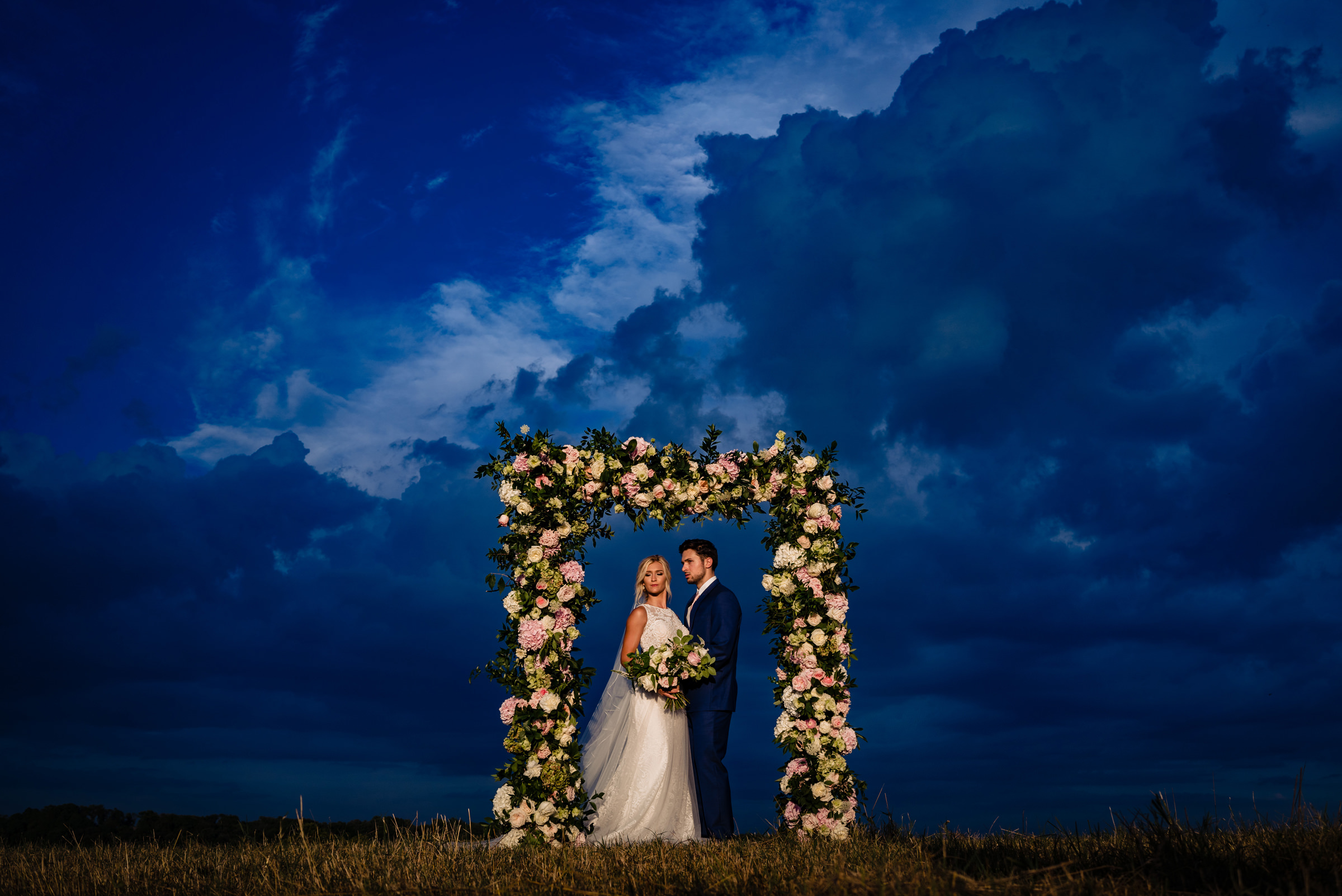 bride and groom portrait under a floral arbor at twilight-Arkansas photographer- photo by Vinson Images