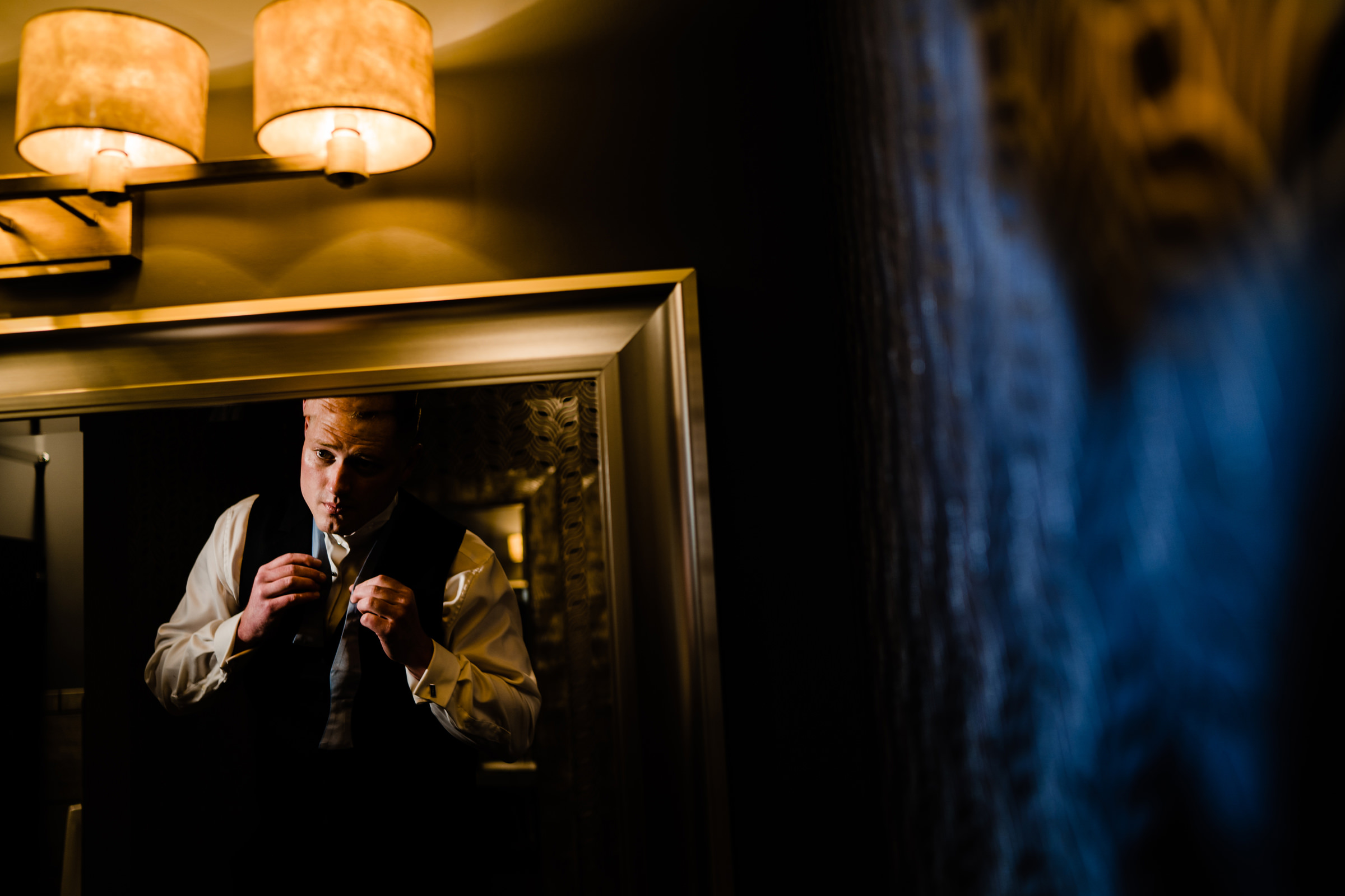 groom putting his tie on and getting ready in mirror-Arkansas photographer- photo by Vinson Images
