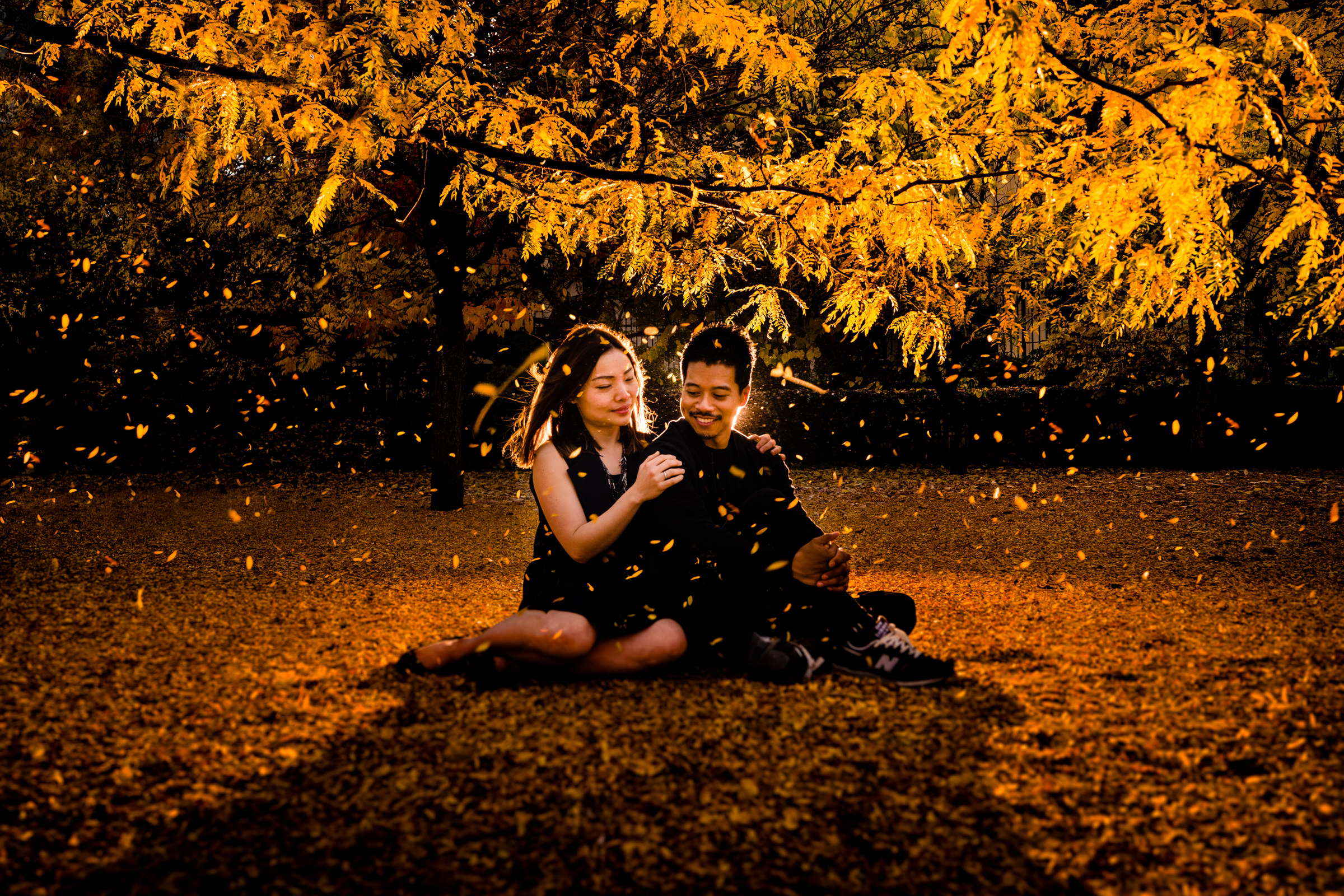 Autumn engagement couple seated on ground among fallen leaves - photo by Vinson Images