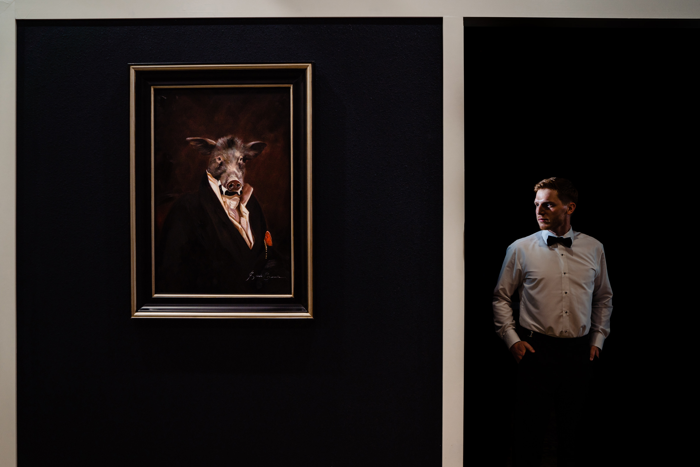 Groom portrait with hanging portrait of pig in a suit - photo by Vinson Images