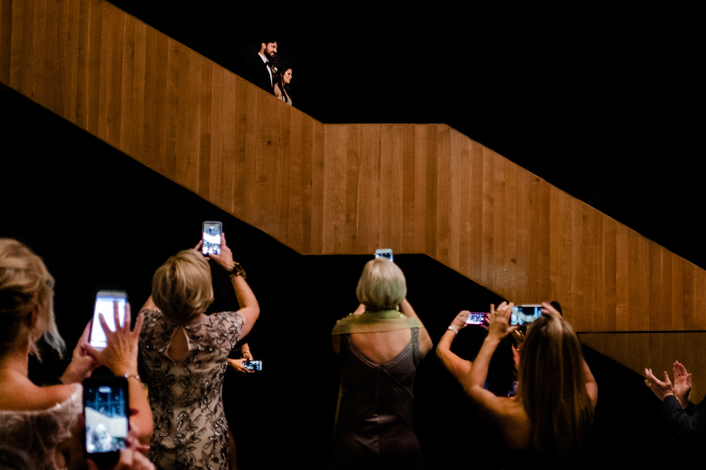 Guests shooting phone photos of couple descending stairs - photo by Vinson Images