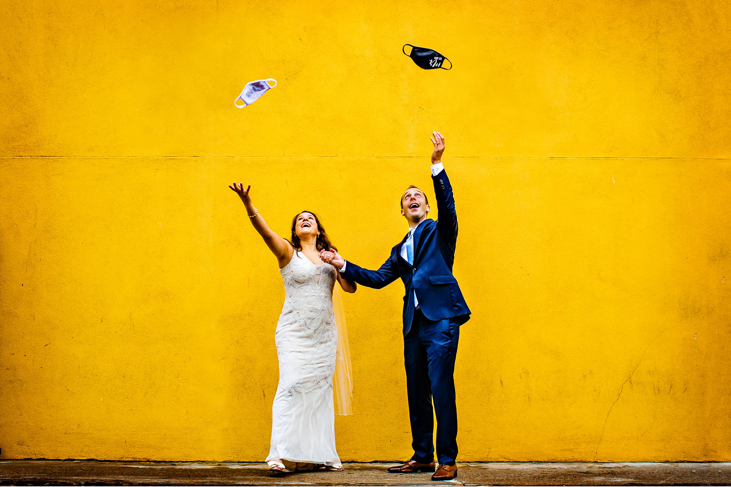 Bride and groom tossing masks in the air - photo by Jeff Tisman Photography