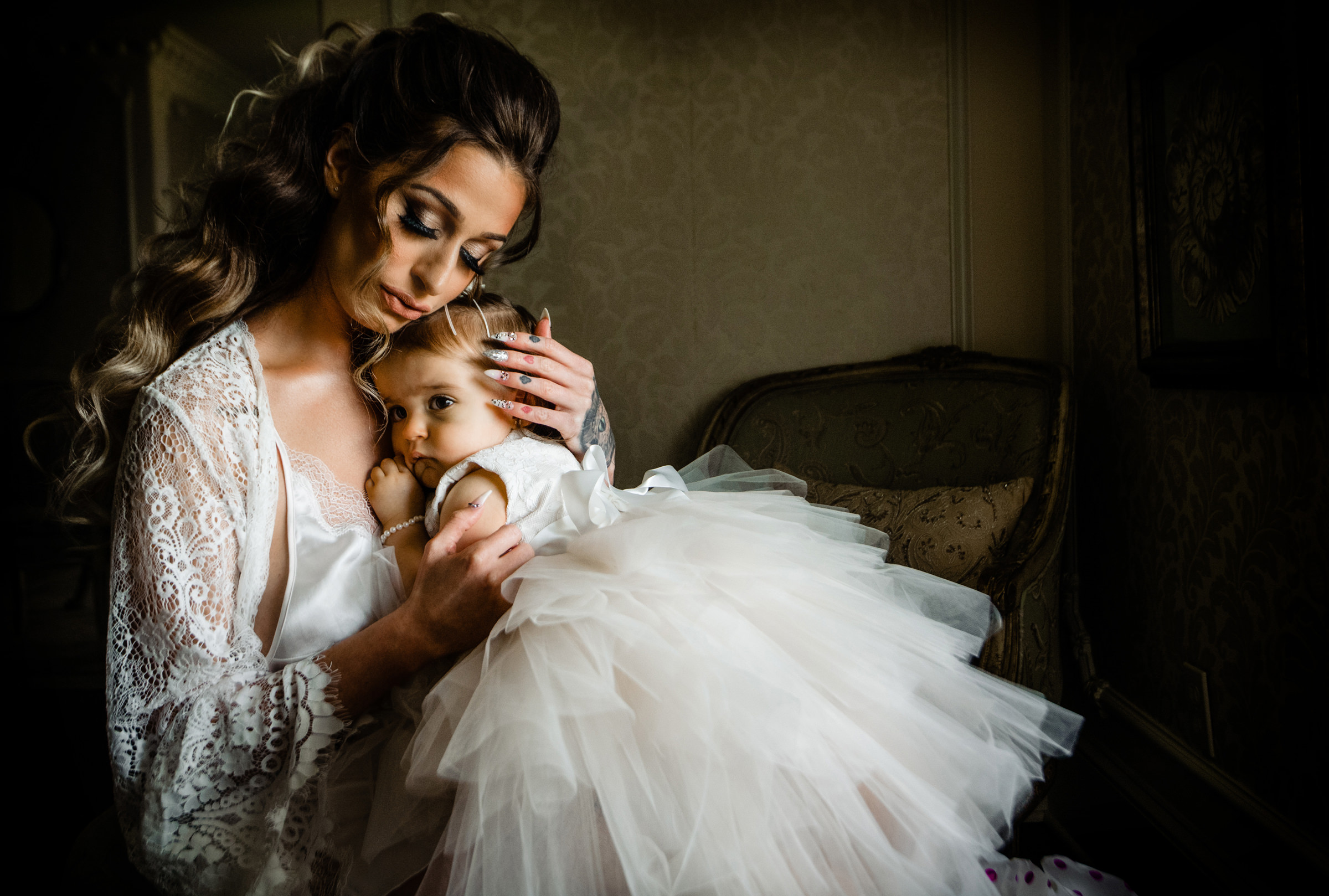 Bride caresses flower girl in white tulle dress  - photo by Jeff Tisman Photography, New York