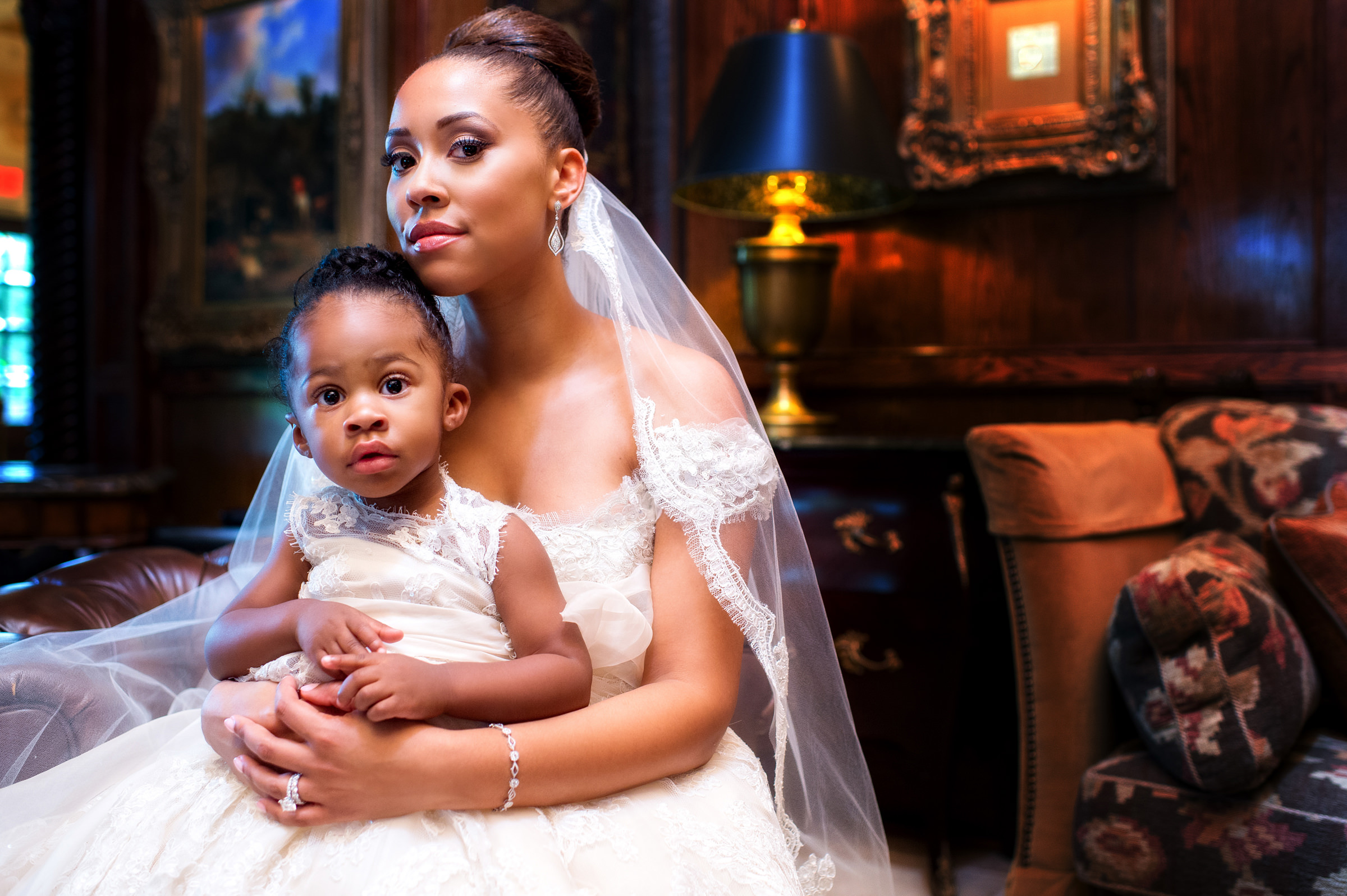 Bride with daughter on her lap wearing veil and lace gown  - photo by Jeff Tisman Photography, New York