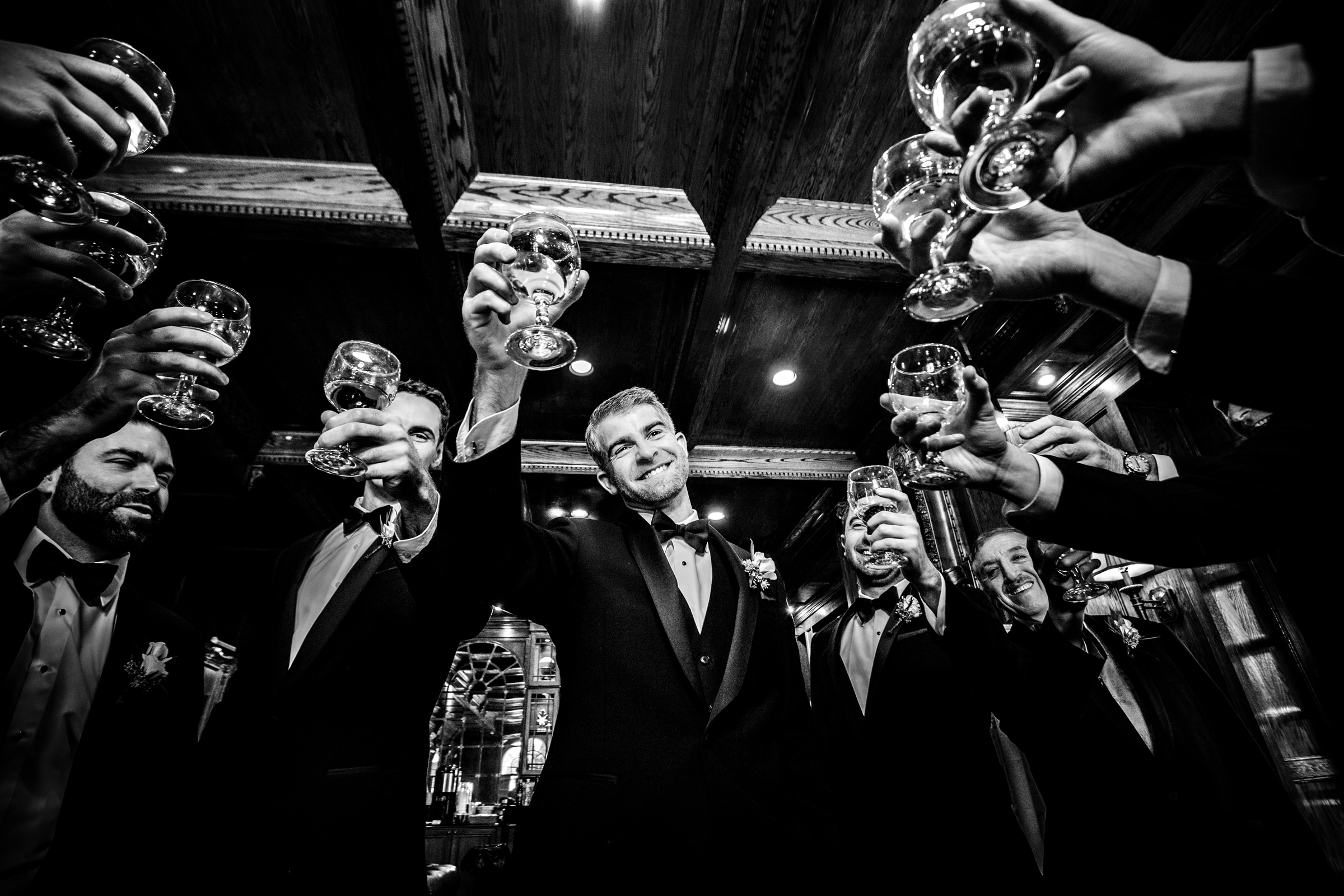 Groom and groomsmen raise a toast - black and white photo by Jeff Tisman Photography, New York