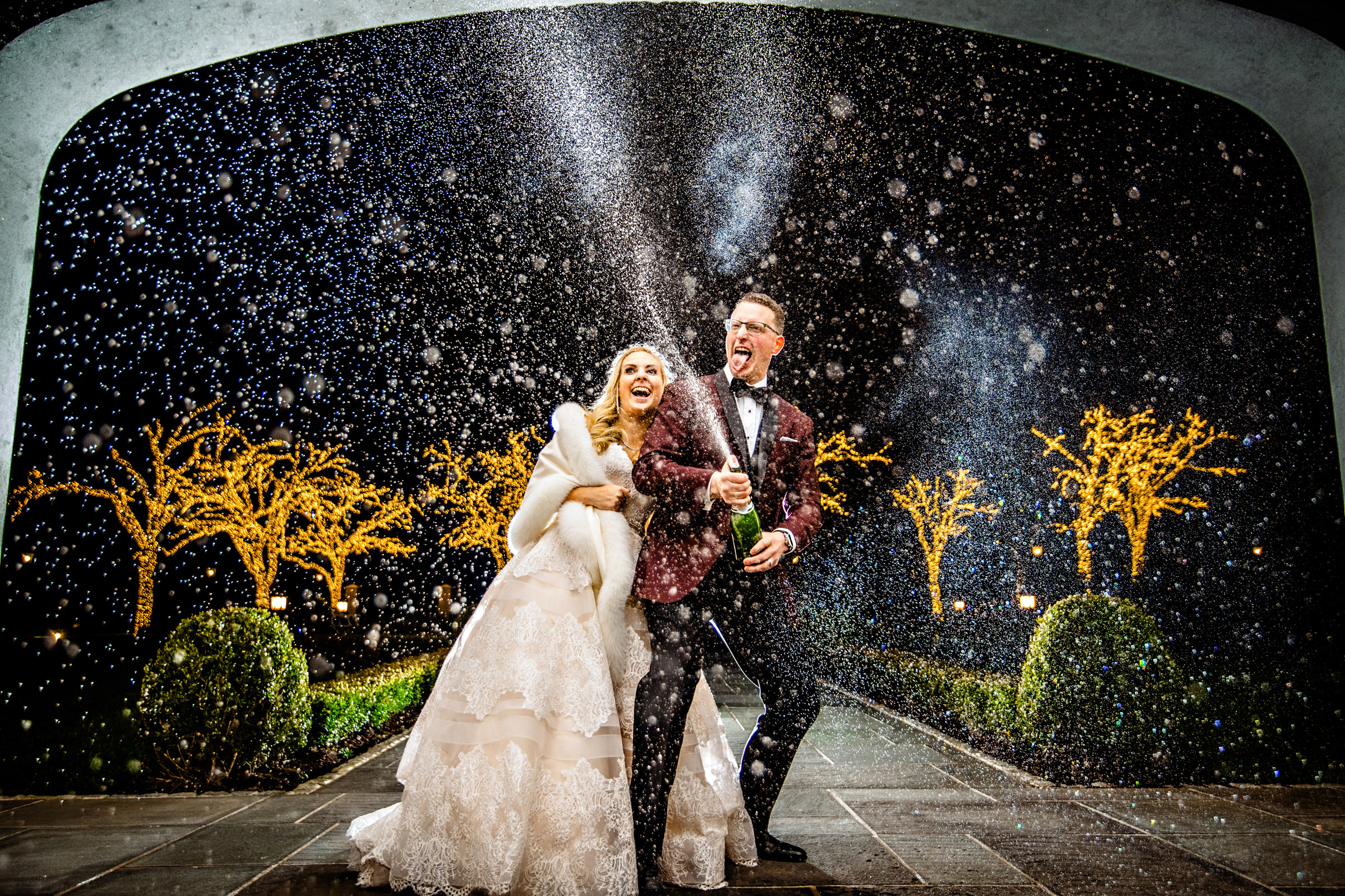 Happy couple corking champagne at night - photo by Jeff Tisman Photography, New York Photographer