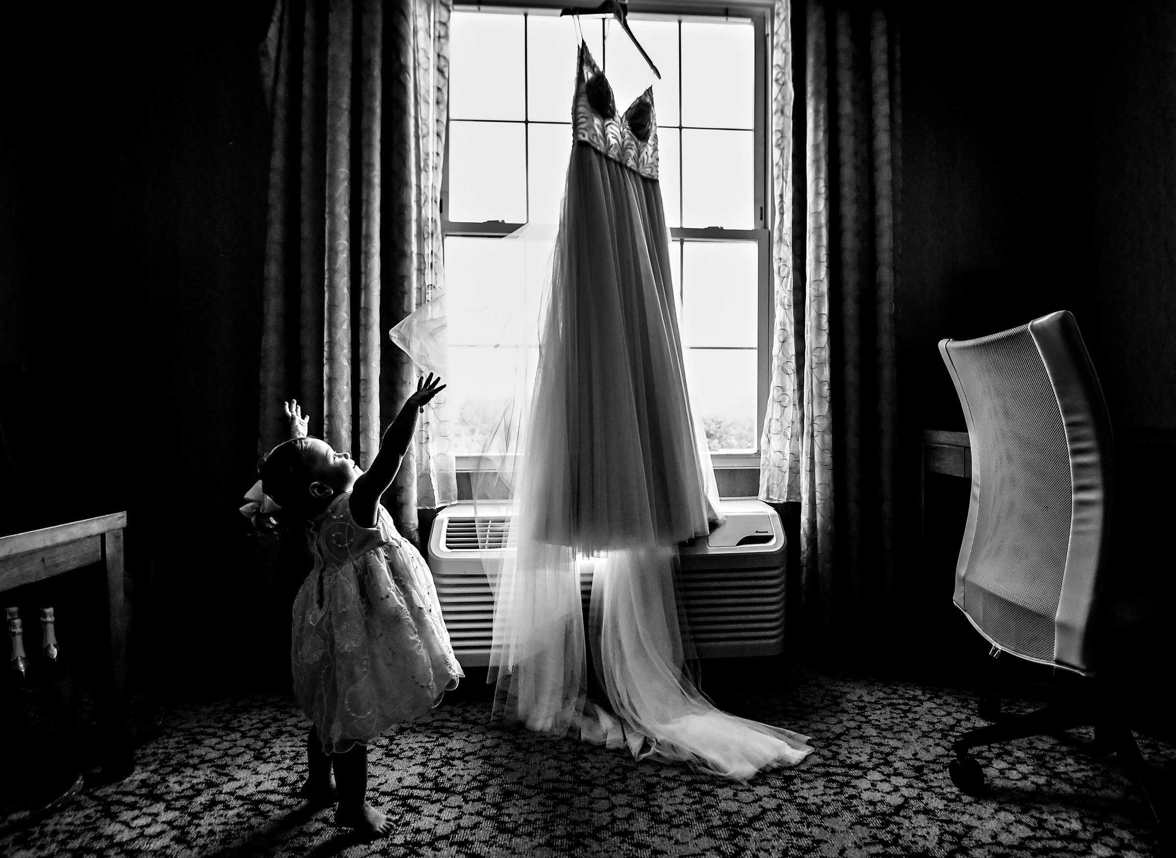 Little girl reaching up toward hanging gown - photo by Jeff Tisman Photography