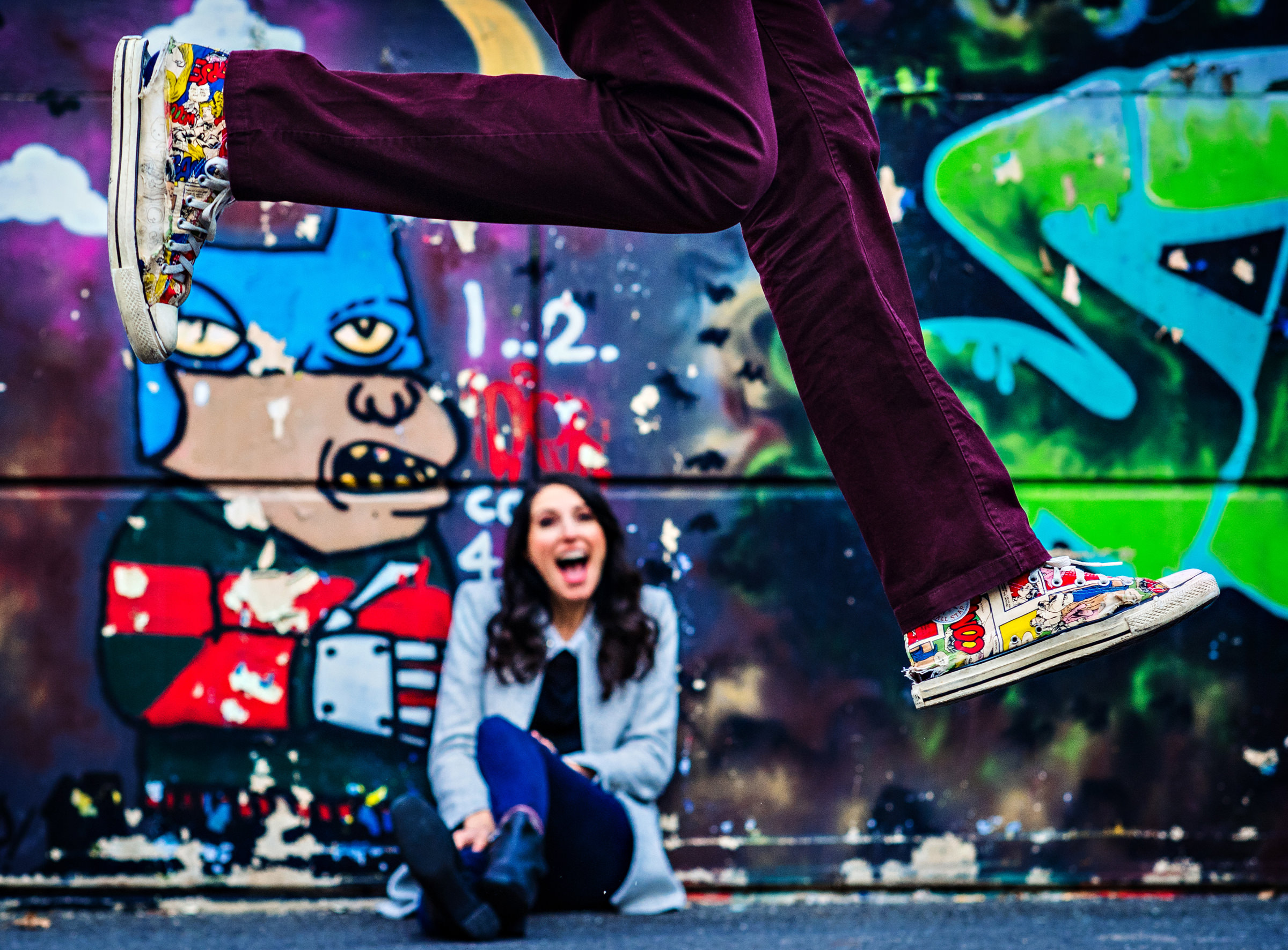 Man leaping over woman against graffiti wall - photo by Jeff Tisman Photography