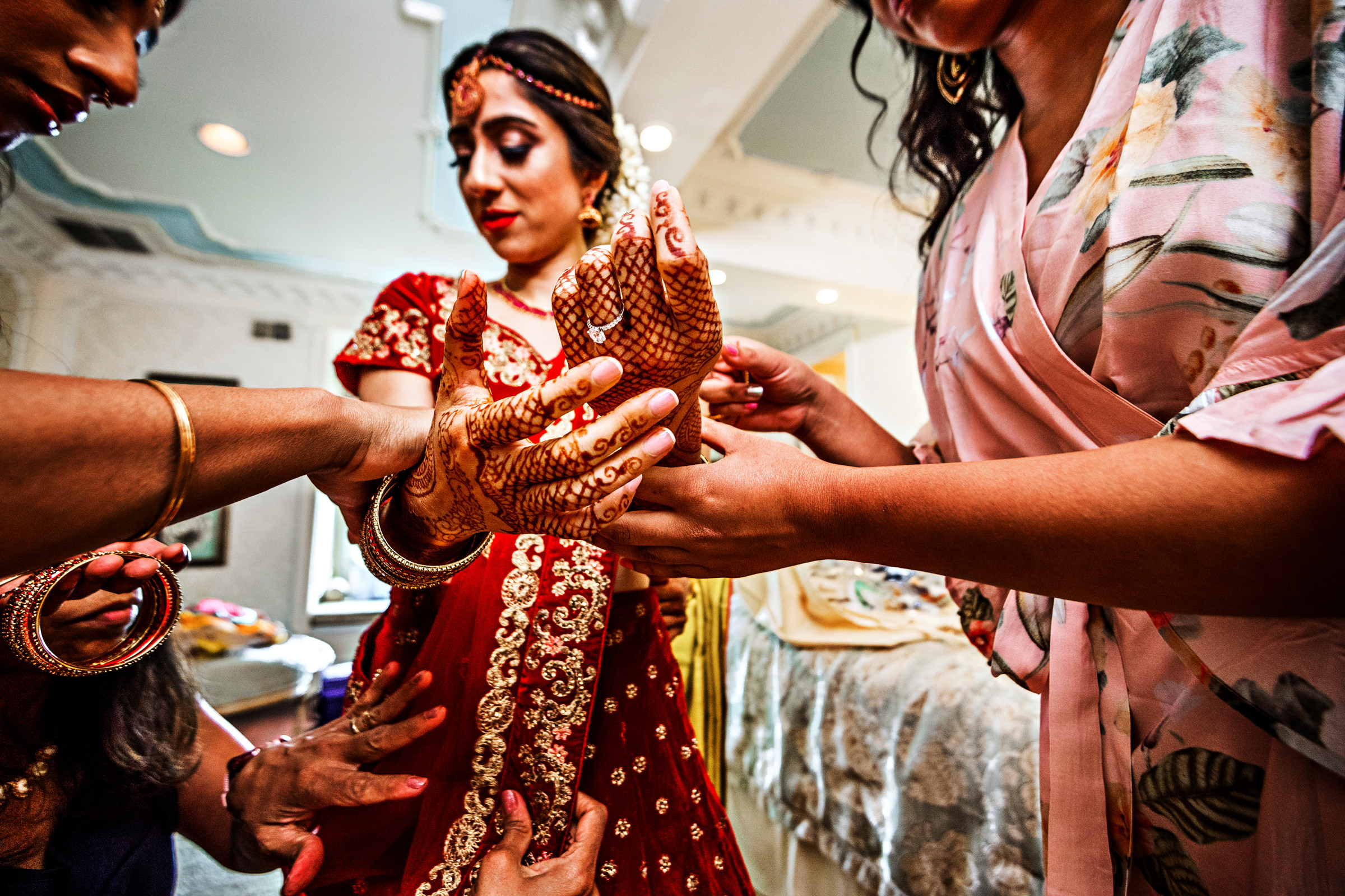 Women attaching bracelets to bride's wrist with henna hands - photo by Jeff Tisman Photography, New York