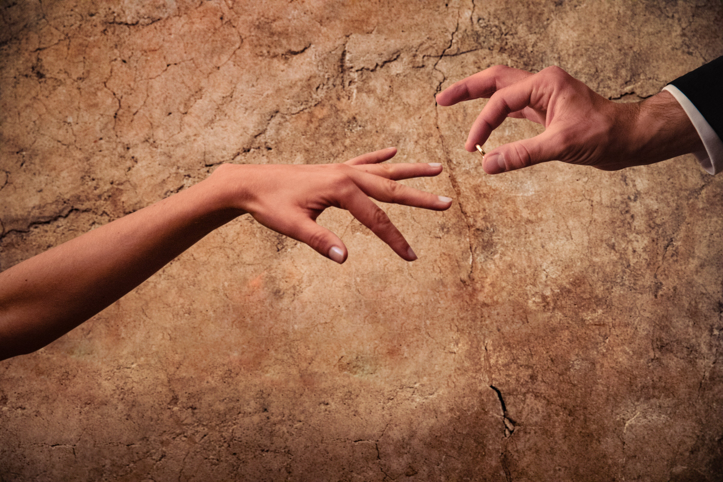 Bride and groom hands with ring against cracked wall - photo by Luca + Marta Gallizio Photography