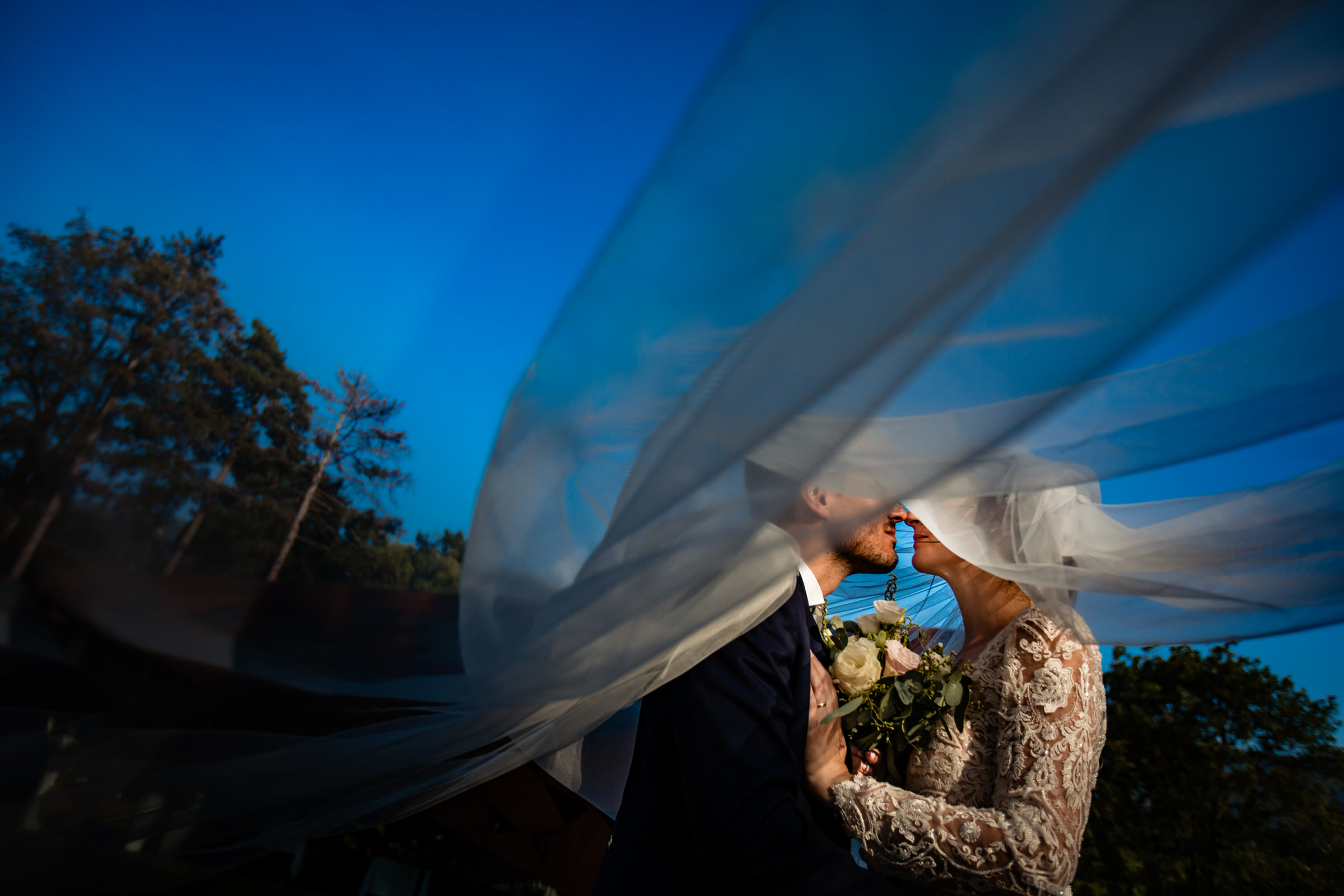 Bride and groom kiss under windblown veil - photo by Luca + Marta Gallizio Photography