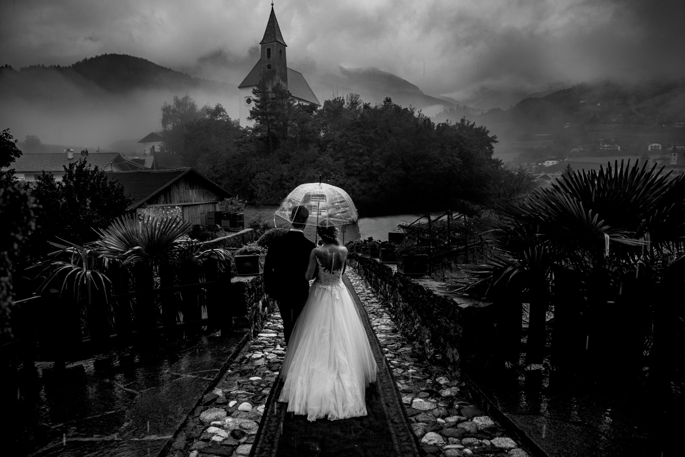 Couple walking under umbrella in Italian landscape  - photo by Luca + Marta Gallizio Photography