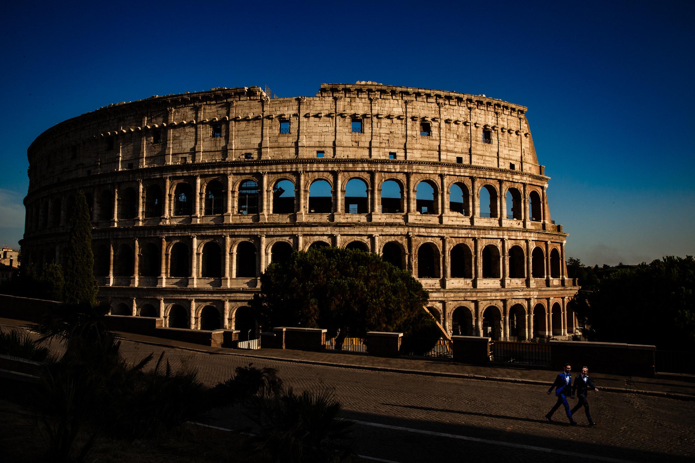 Grooms walking near coliseum - photo by Luca + Marta Gallizio Photography