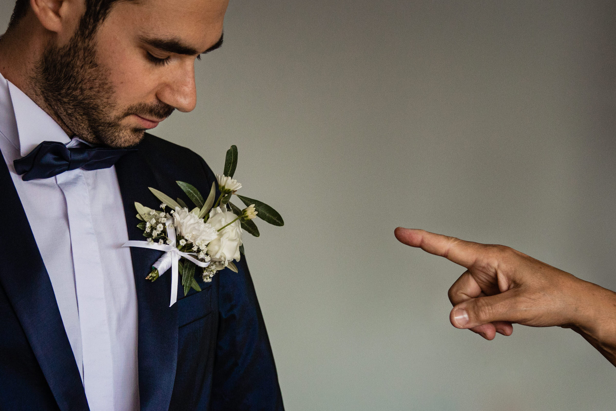 Pointing to the boutonniere - photo by Luca + Marta Gallizio Photography