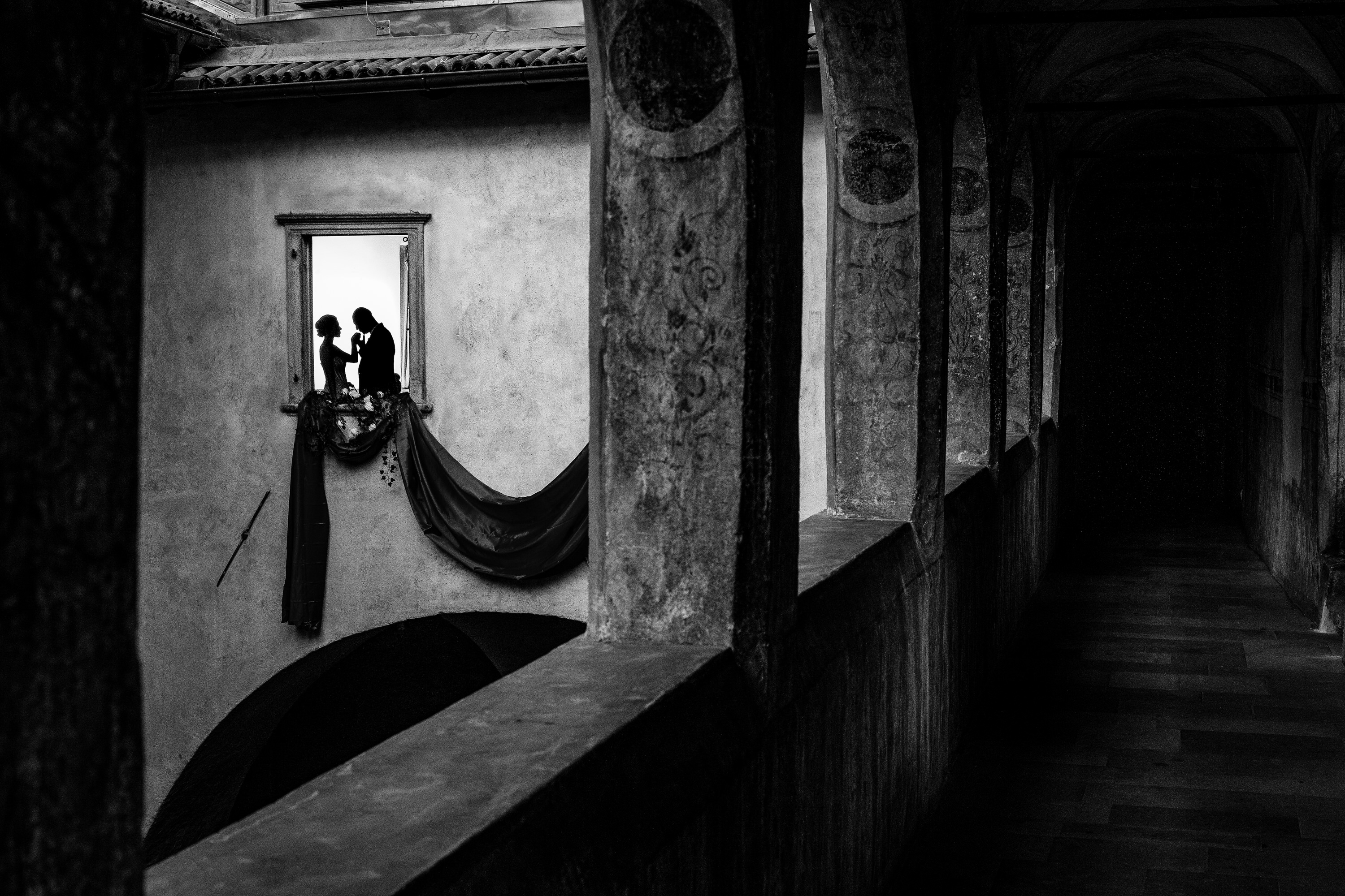 Silhouette couple through window at Castle Mareccio - photo by Luca + Marta Gallizio Photography