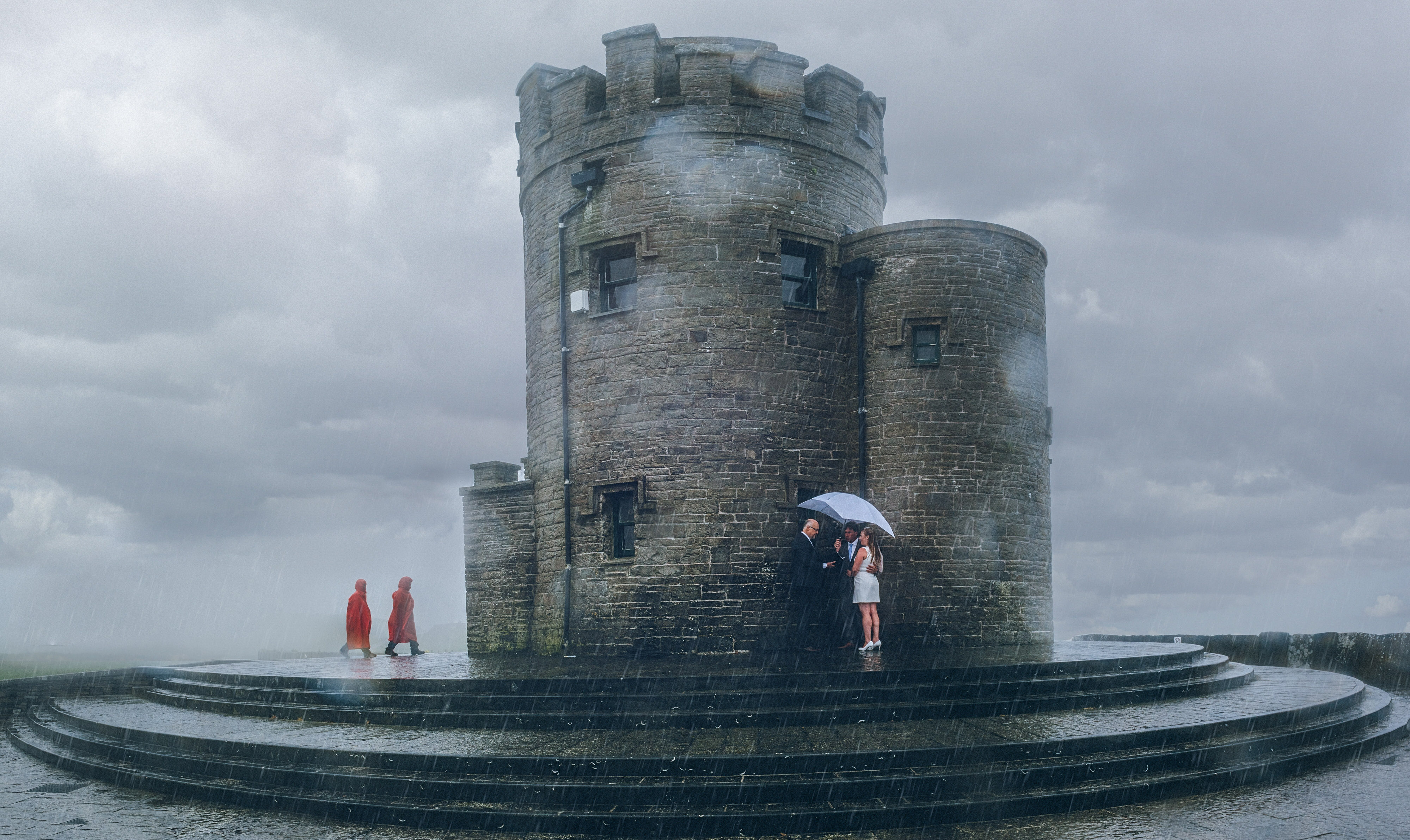 Couple under umbrella at castle - photo by John Gillooley