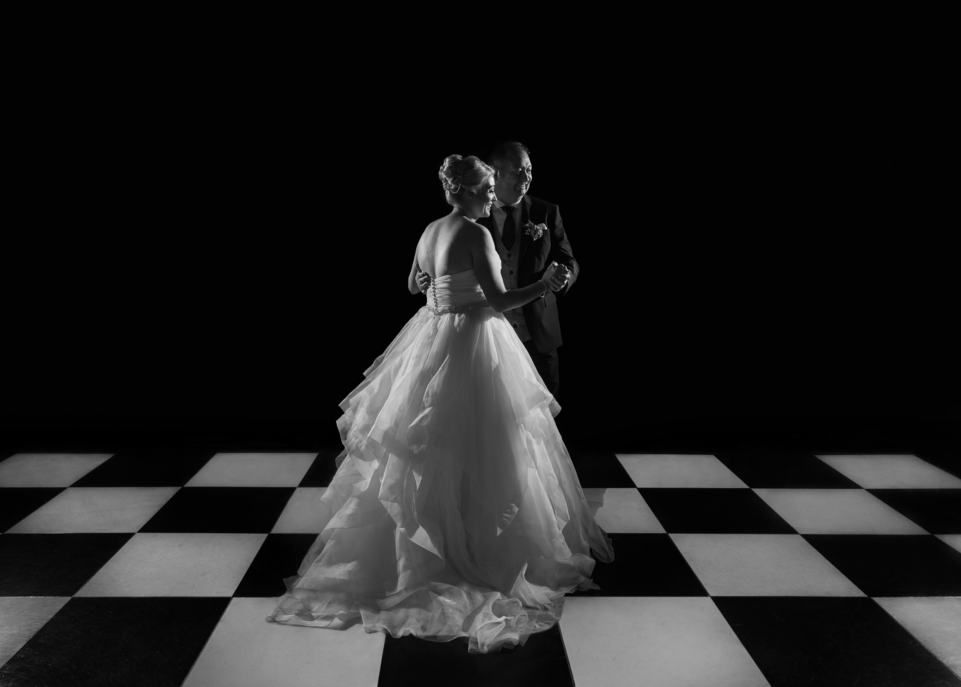 bride and groom first dance on checkered dance floor- photo by John Gillooley, ireland