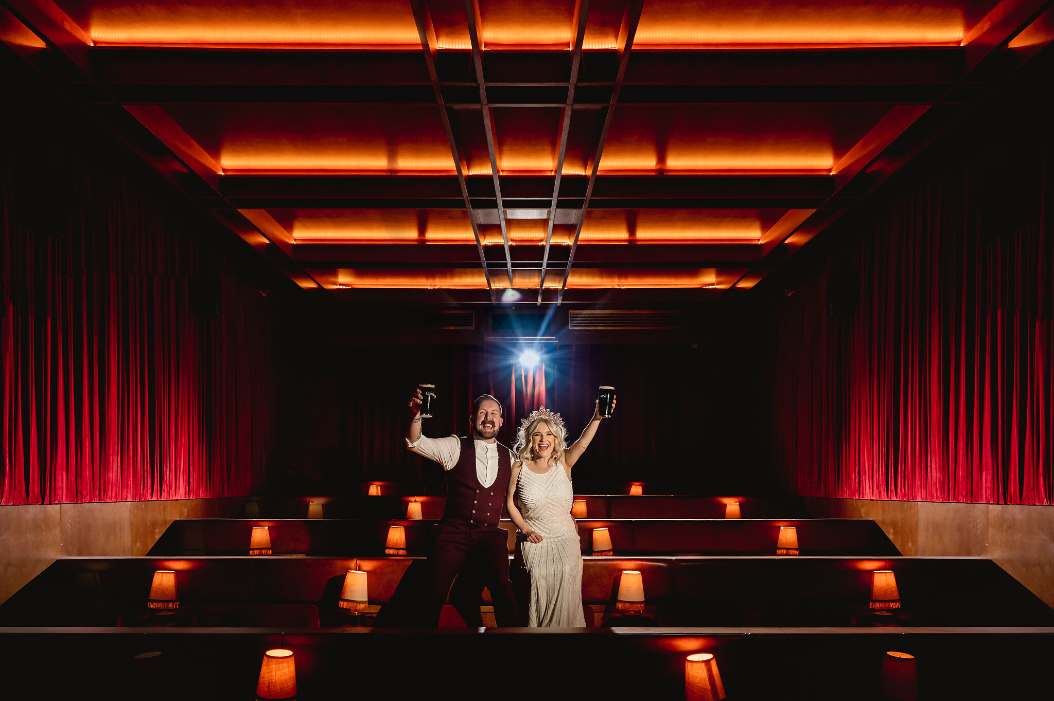 bride and groom portrait toasting with guinness in movie theater- photo by John Gillooley, ireland
