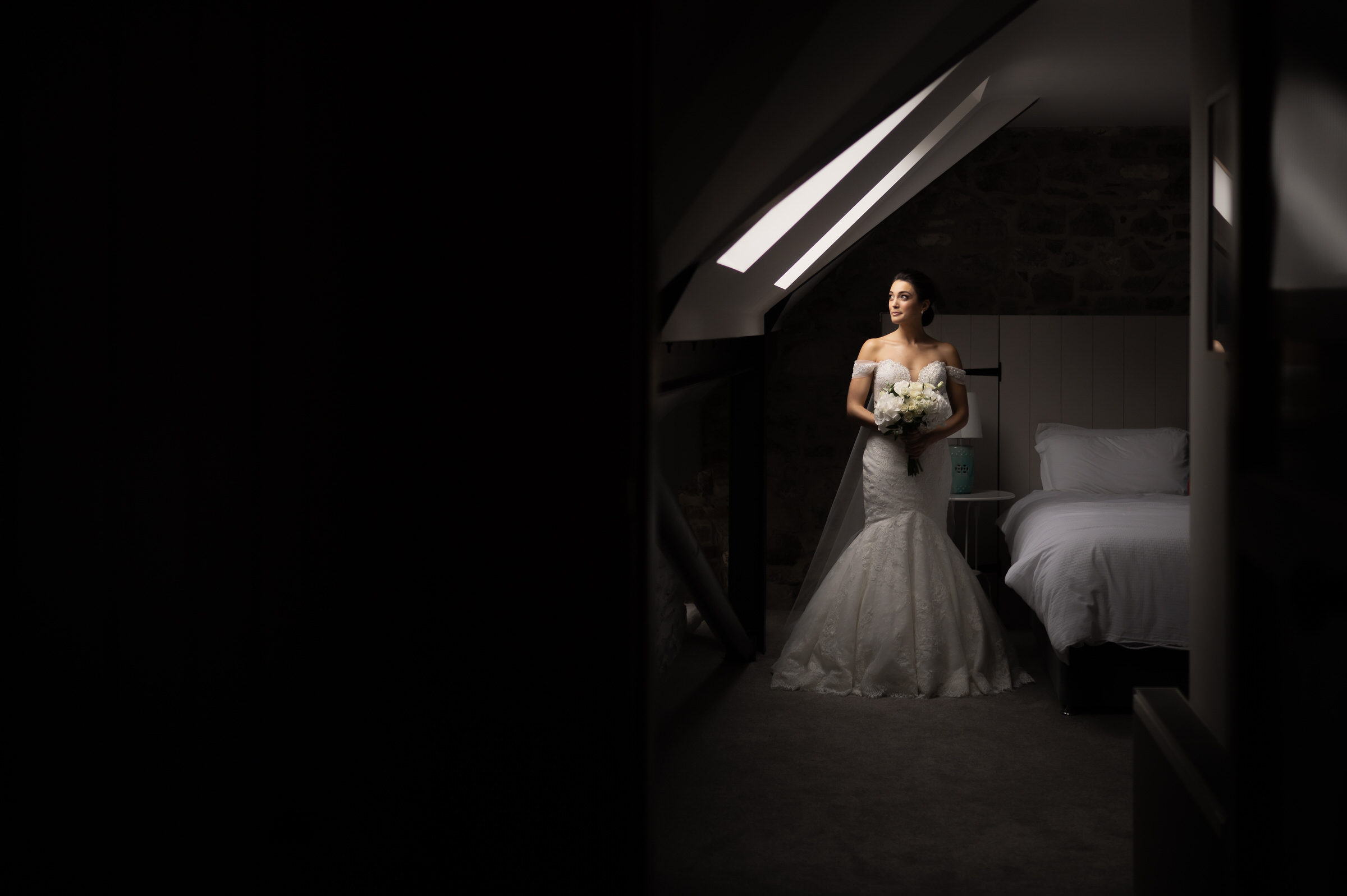 Bride by bed in attic room - photo by John Gillooley
