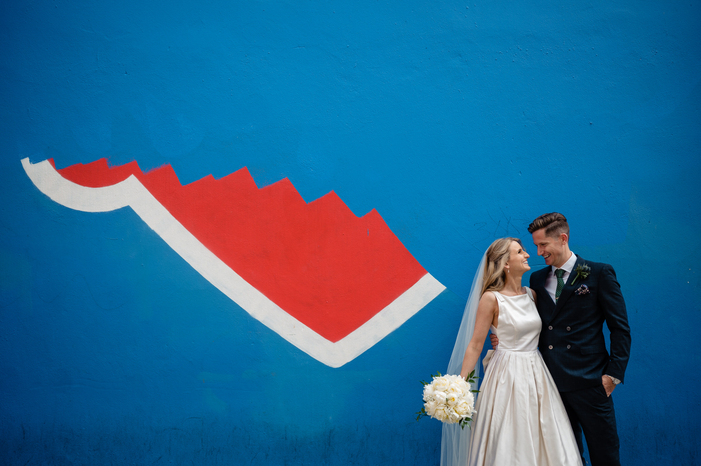 Couple portrait against dramatic wall art - photo by John Gillooley
