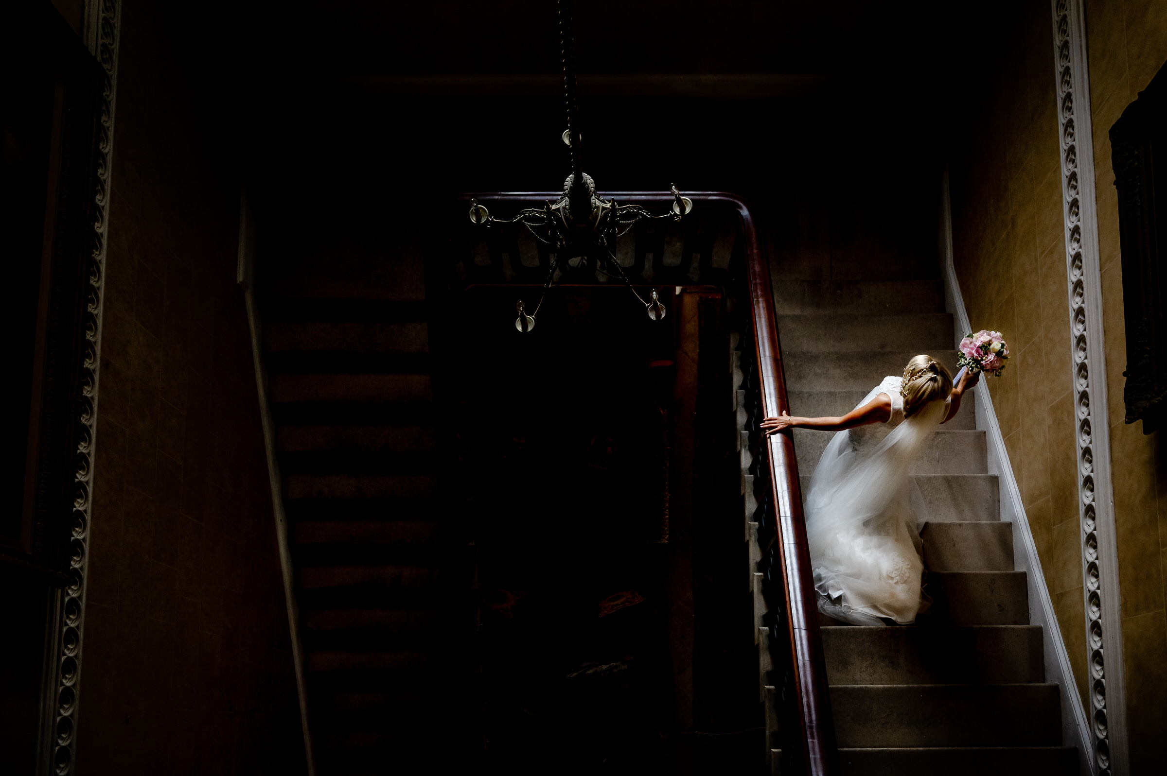 Creative shot of bride on darkened staircase - photo by John Gillooley