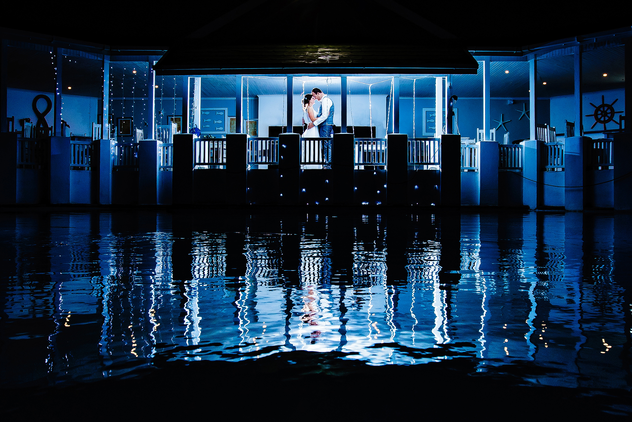 Couple against blue shimmering water - photo by Ruan Redelinghuys Photography