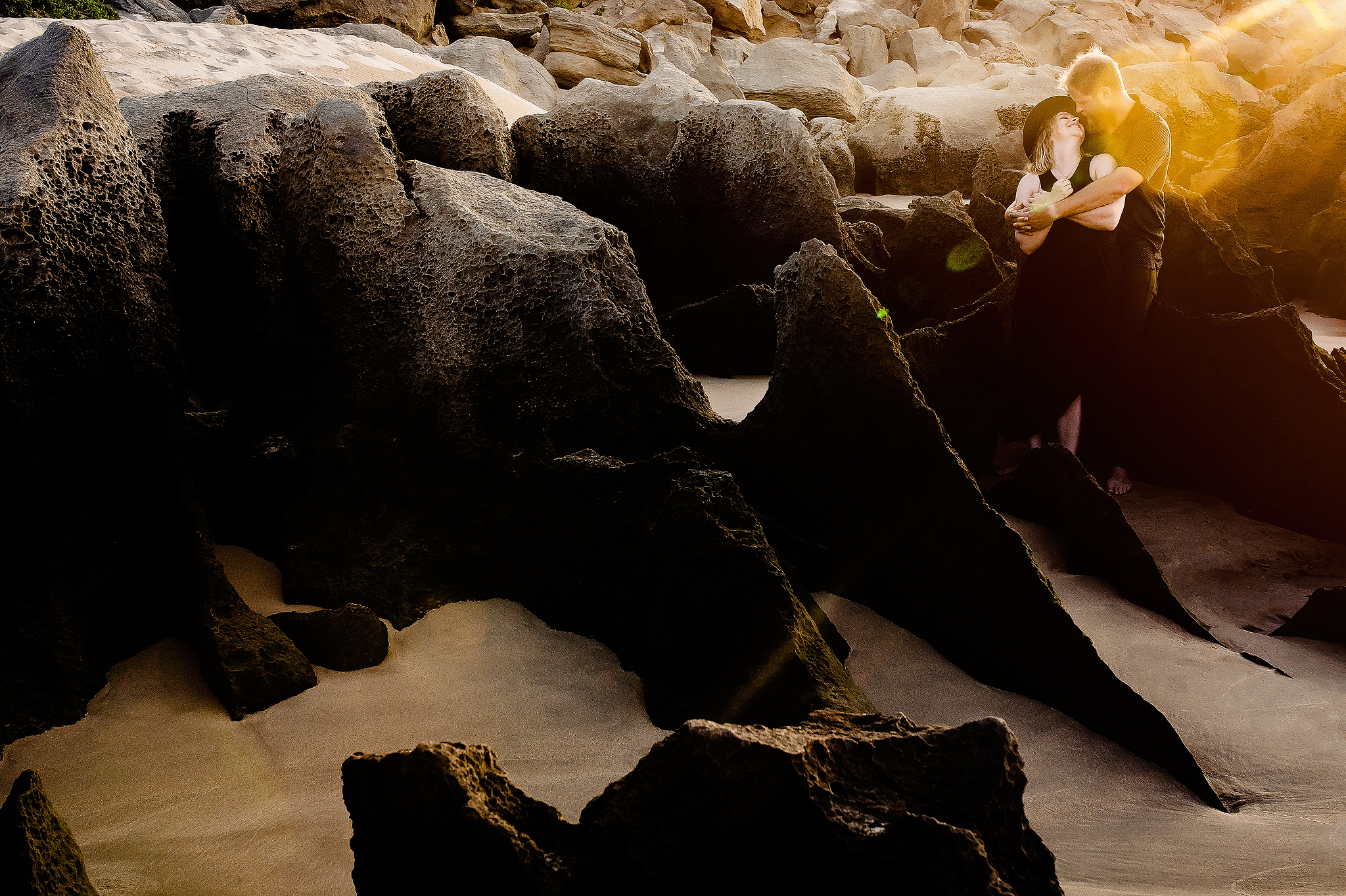 Engagement portrait among unusual rock formations on sand - photo by Ruan Redelinghuys Photography