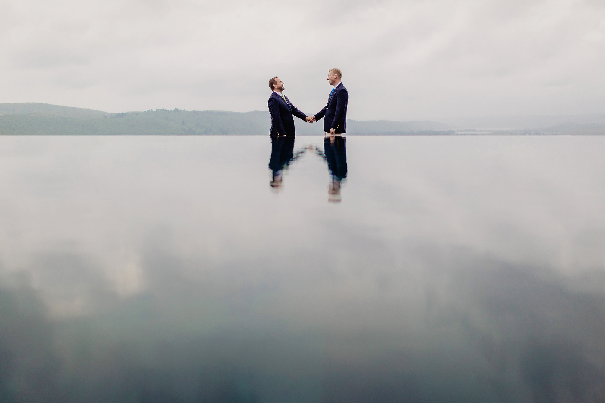 Groom and groom reflected in water - photo by Ruan Redelinghuys Photography