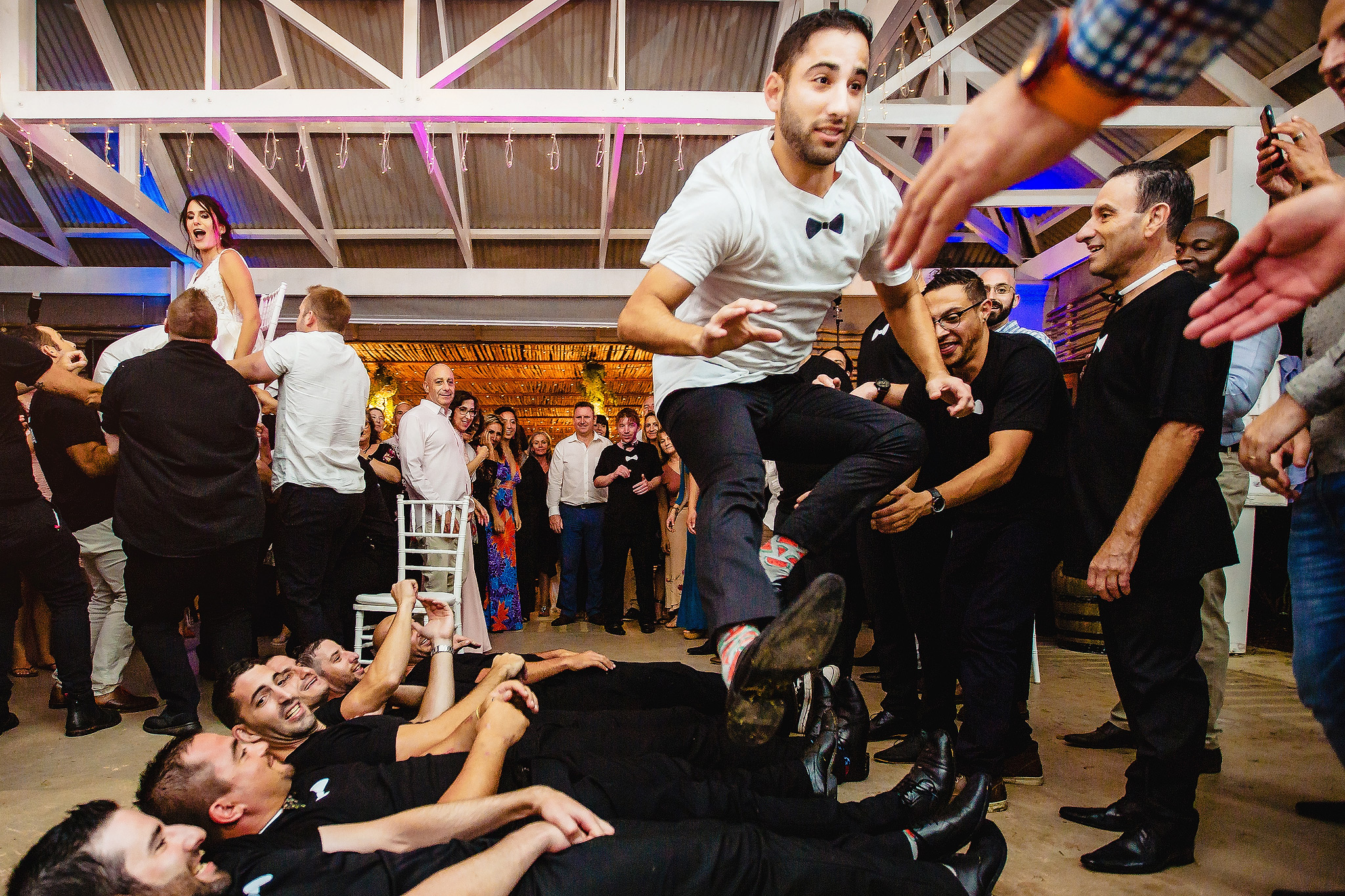 Groom leaping over prone groomsmen - photo by Ruan Redelinghuys Photography