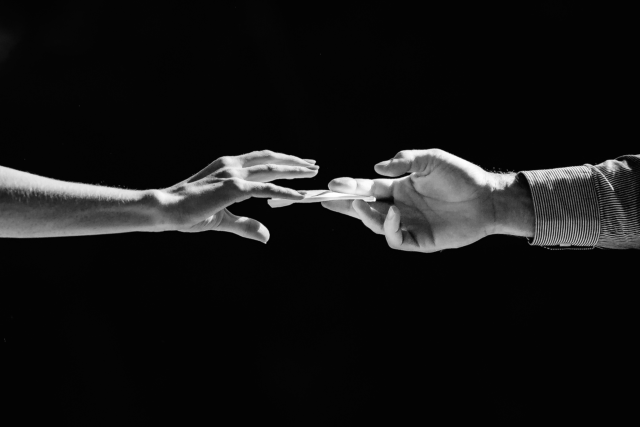 Hands passing a note - photo by Ruan Redelinghuys Photography