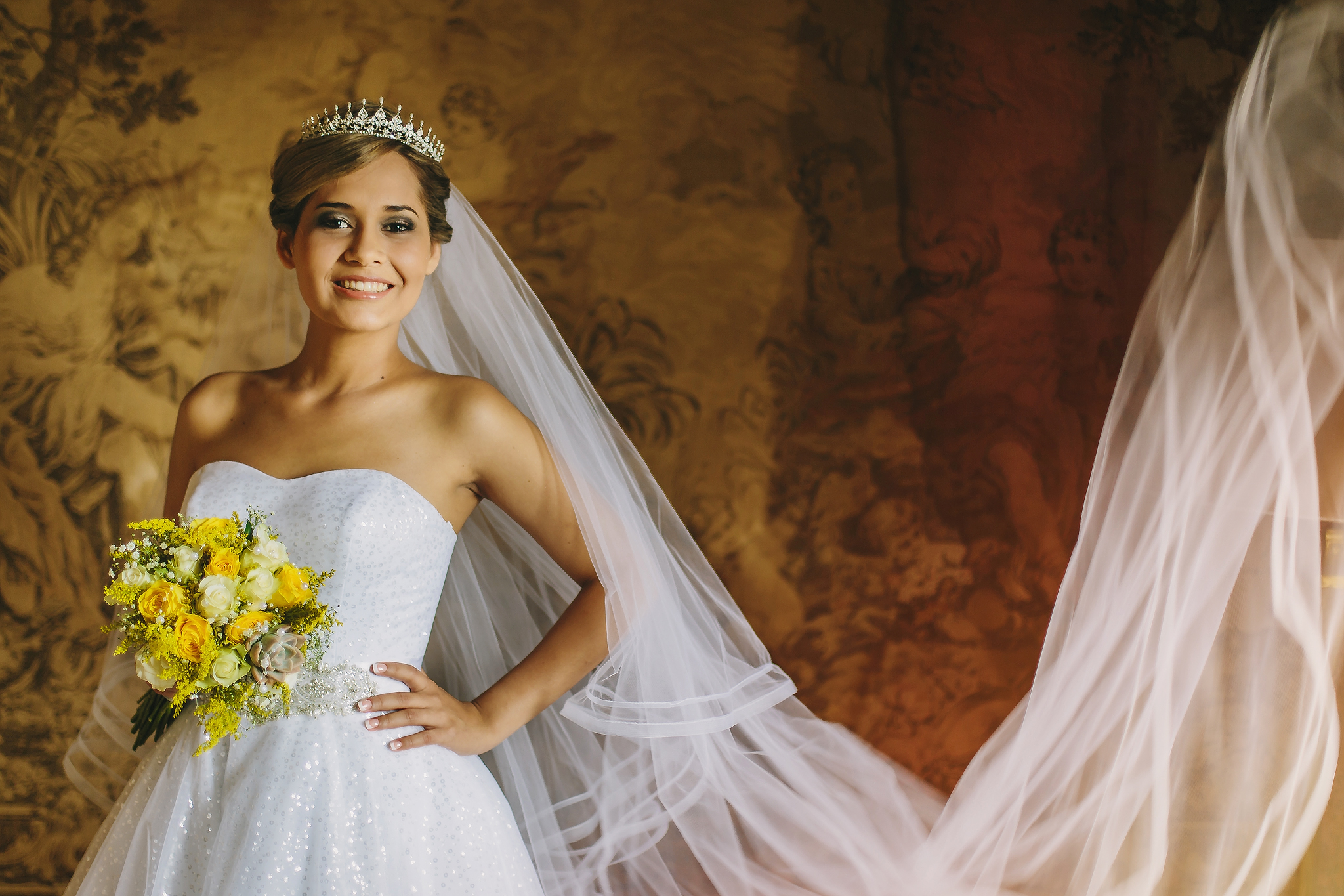 Smiling bride portrait with long veil against tapestry - photo by Ruan Redelinghuys Photography