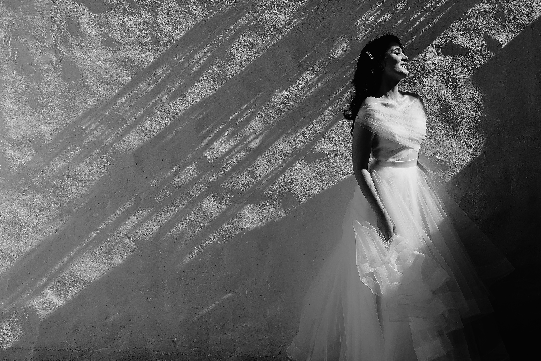 Bride in chiffon gown against wall with shadows - photo by Ruan Redelinghuys Photography