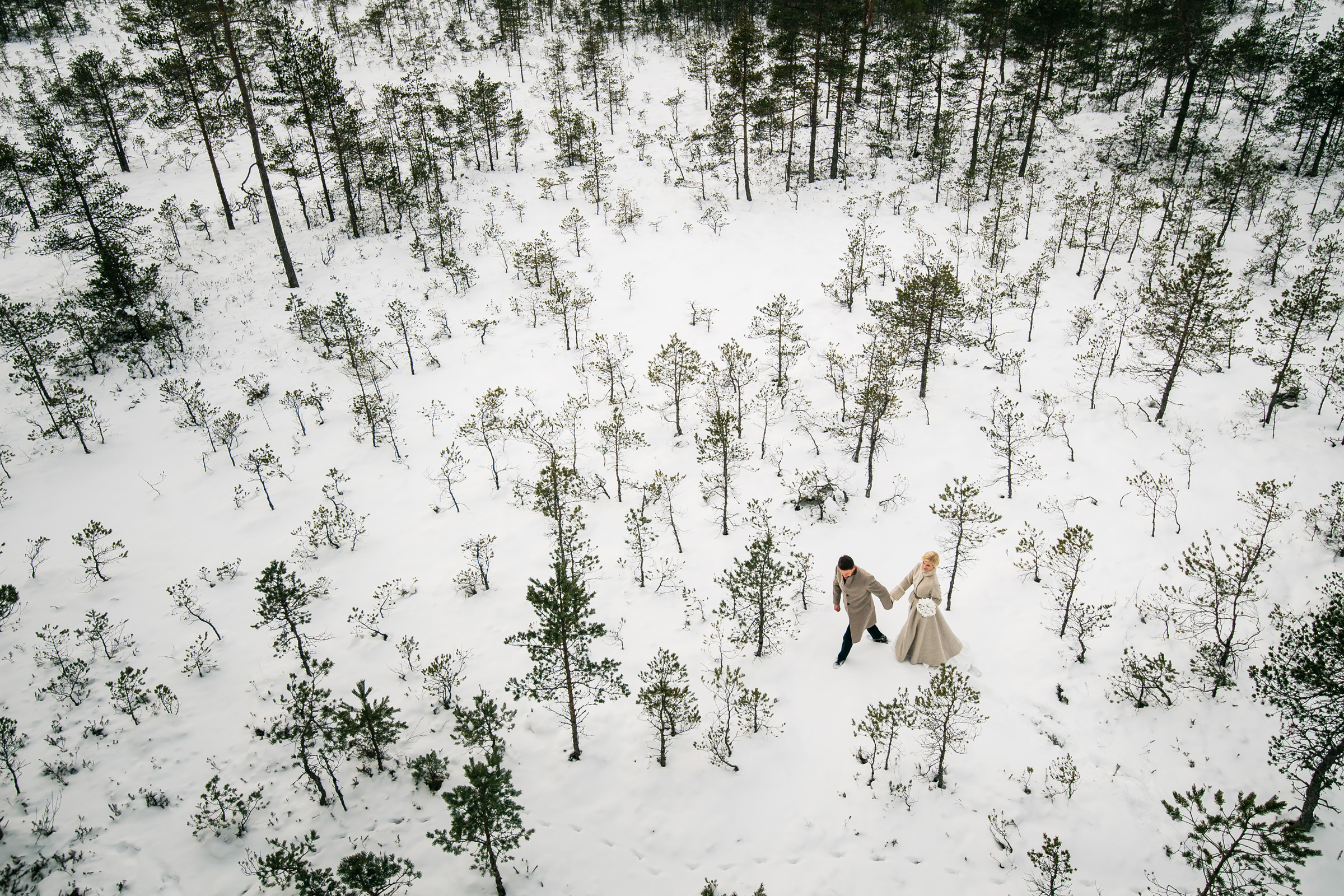 Aerial shot of couple in snow among trees in Estonia - photo by M&J Studios