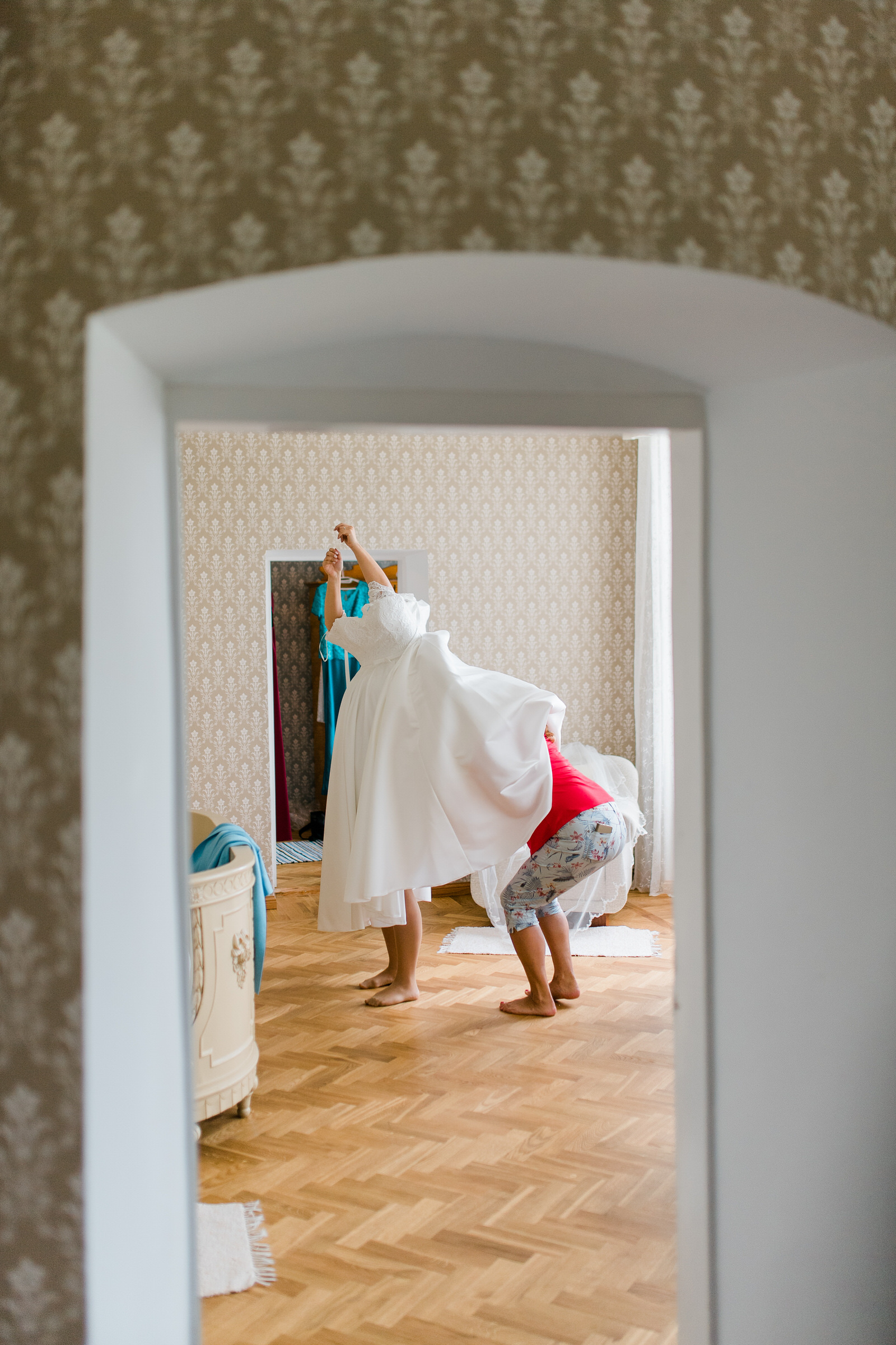 Comical headless bride getting into her gown - photo by M&J Studios