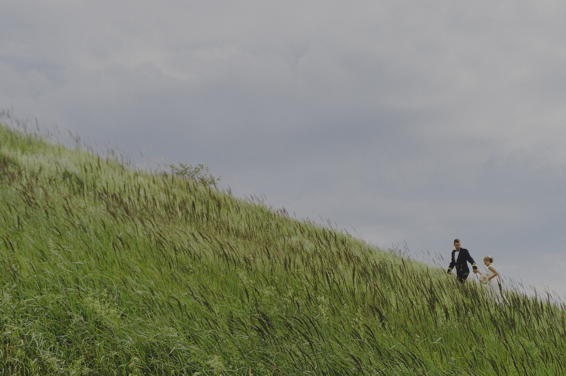 Couple climbing grassy slop in Estonia - photo by M&J Studios