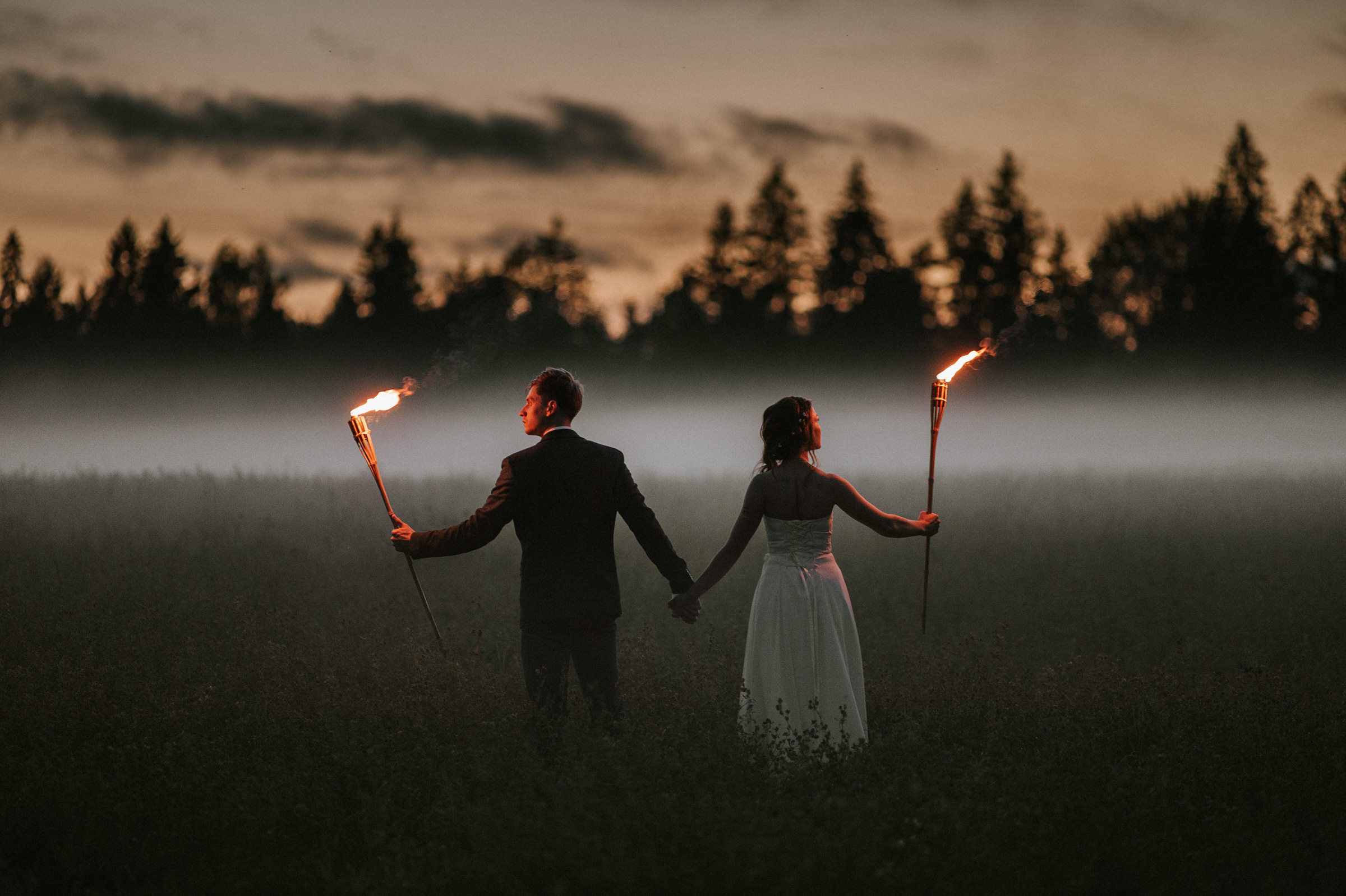 Couple holding torches against the fog in Estonia - photo by M&J Studios