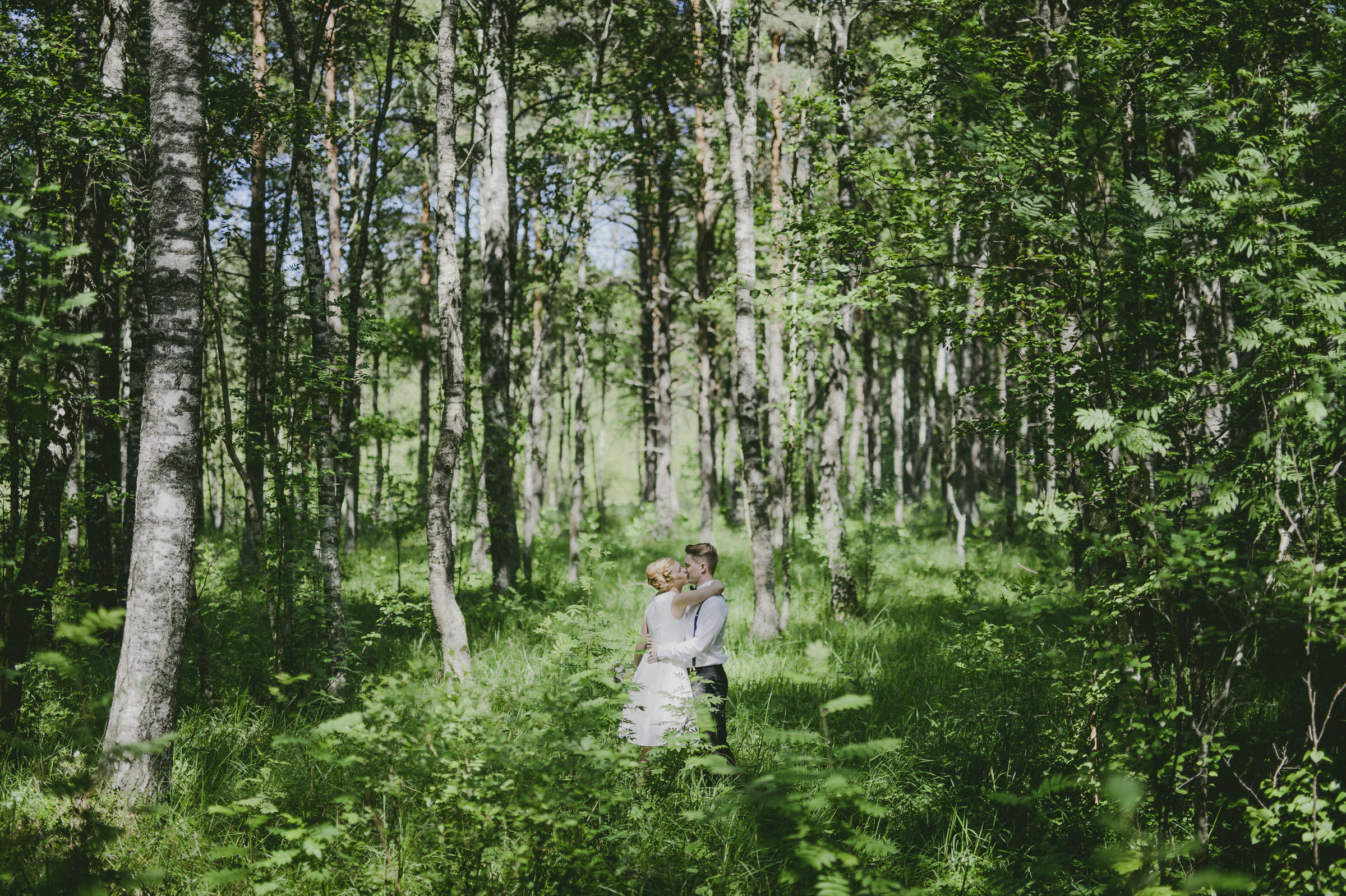 Couple kiss in shimmering Estonian forest - photo by M&J Studios