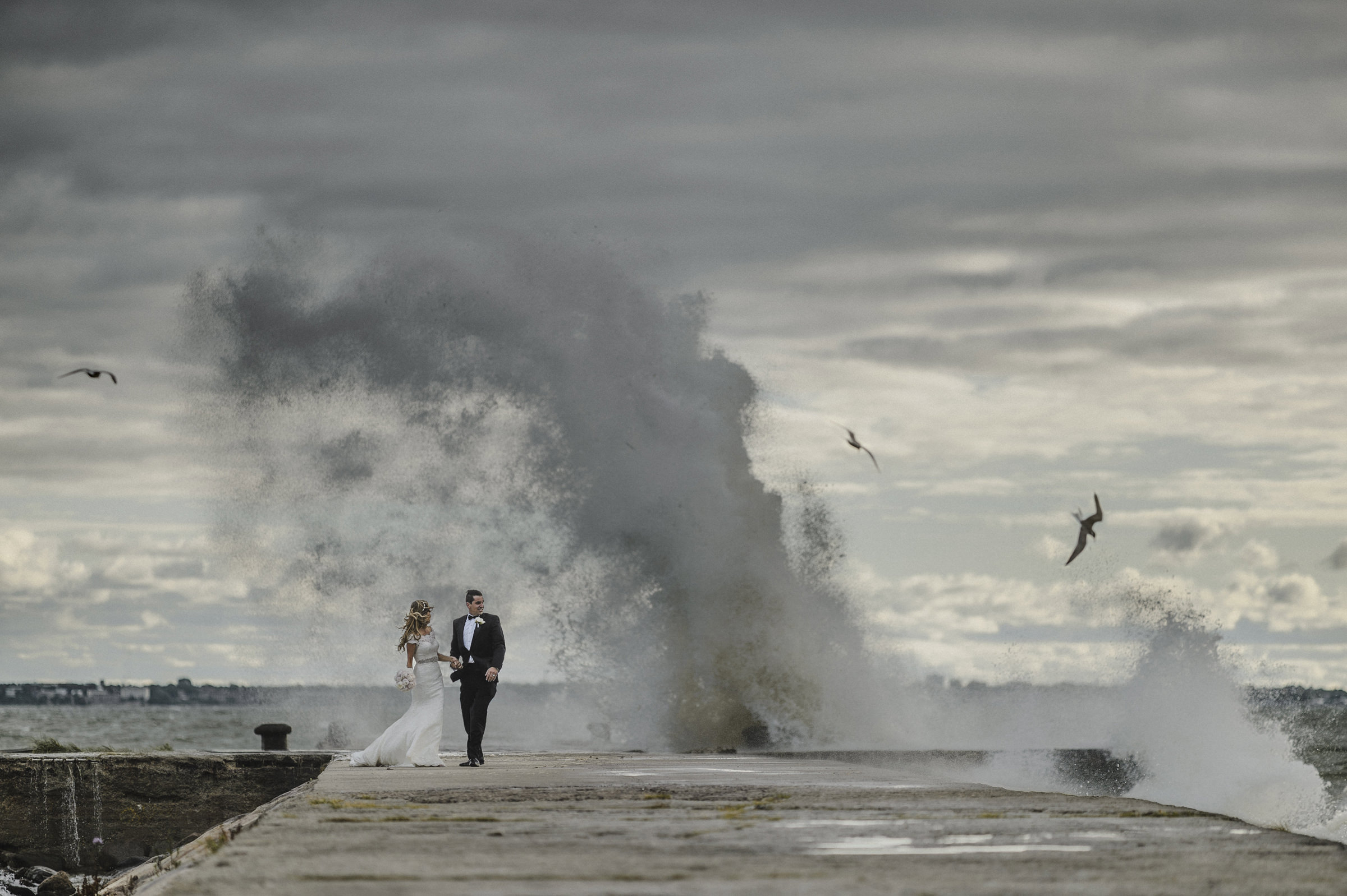 Couple on dock against wild surf in Estonia - photo by M&J Studios