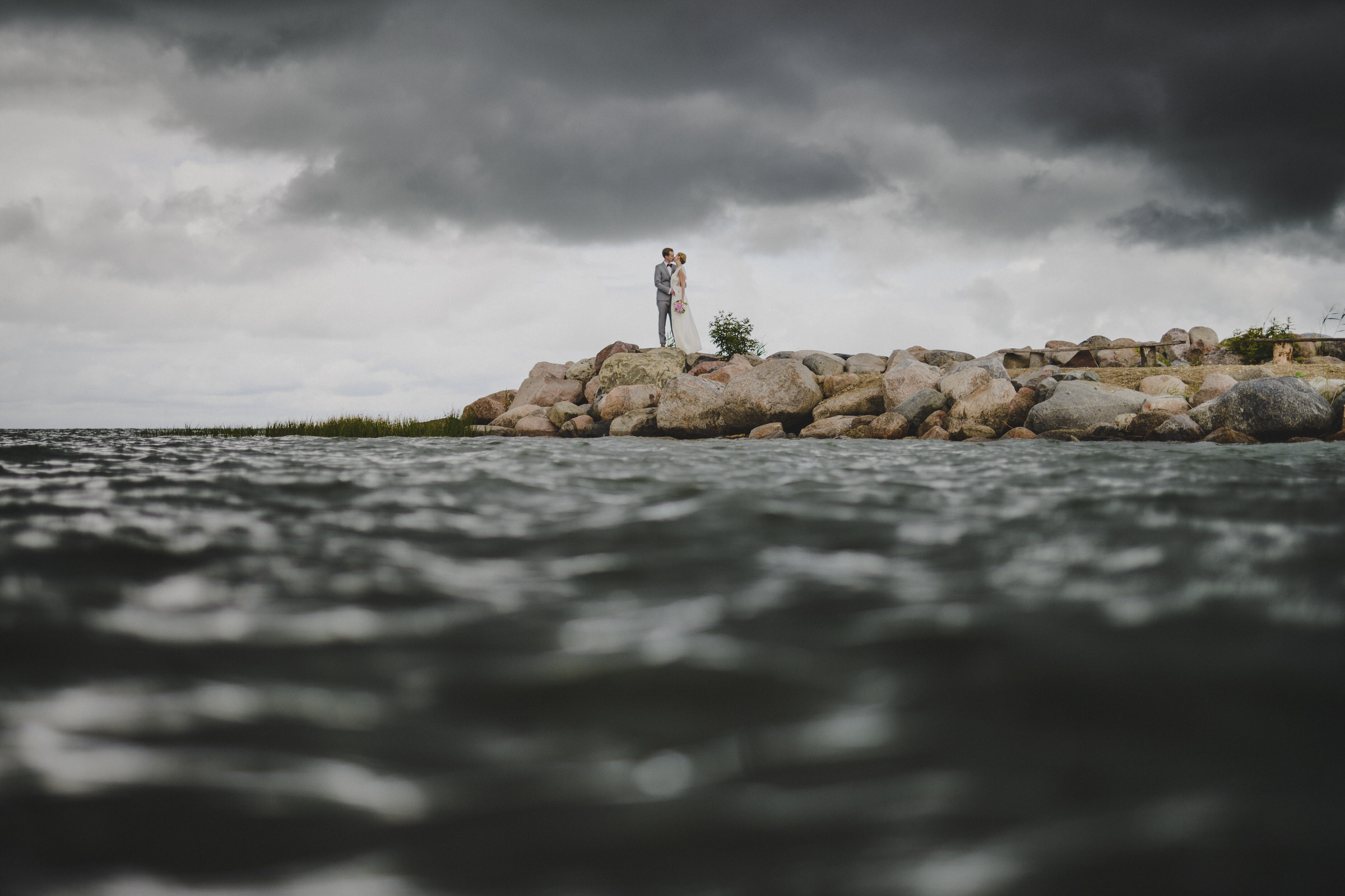 Couple on rock against water in Estonia - photo by M&J Studios