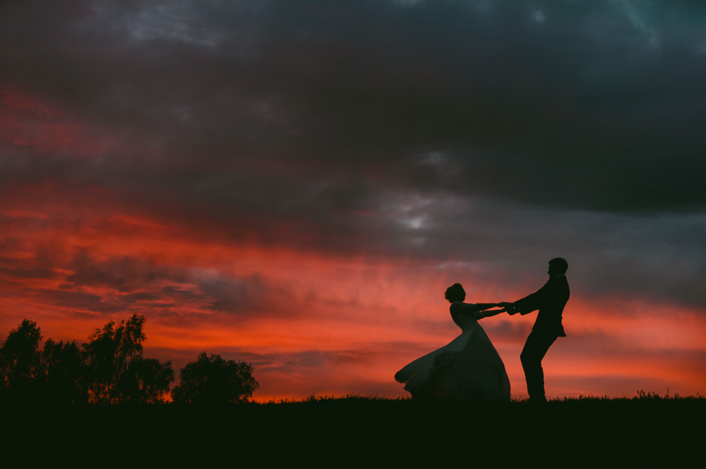 Silhouette of bride and groom dancing against red sky - photo by M&J Studios - Estonia