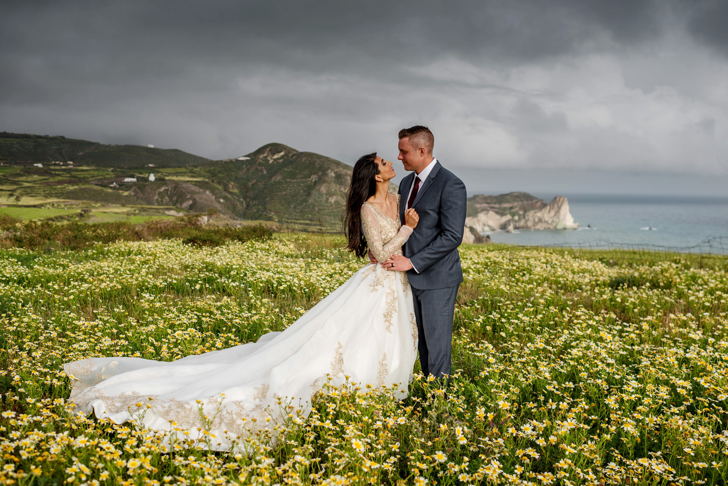 Couple in epic field of flowers against cliffs - photo by Barbie Hull Photography