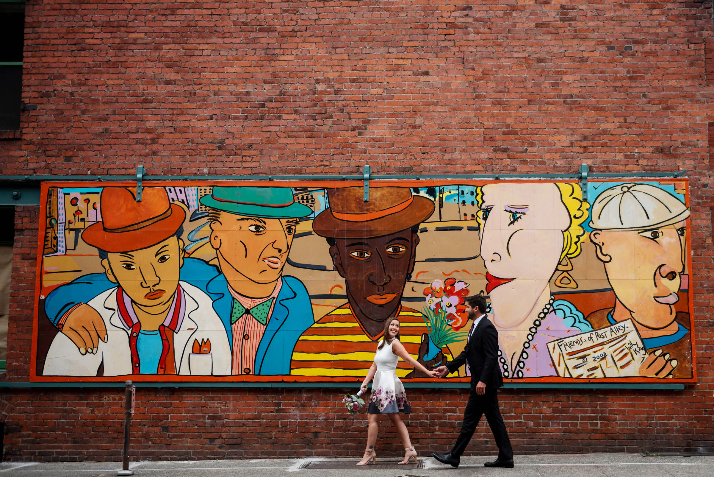 Couple walk past urban mural - photo by Barbie Hull Photography