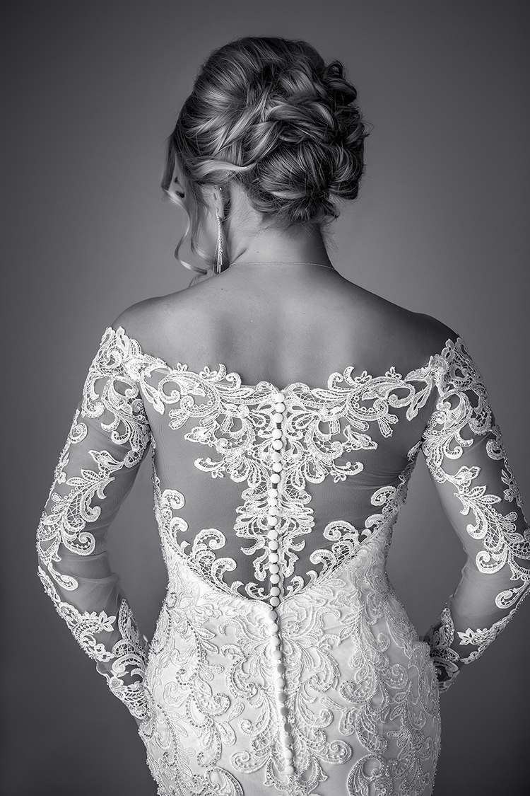 Back of bride in white applique lace dress and updo - photo by Amber Henry Photography