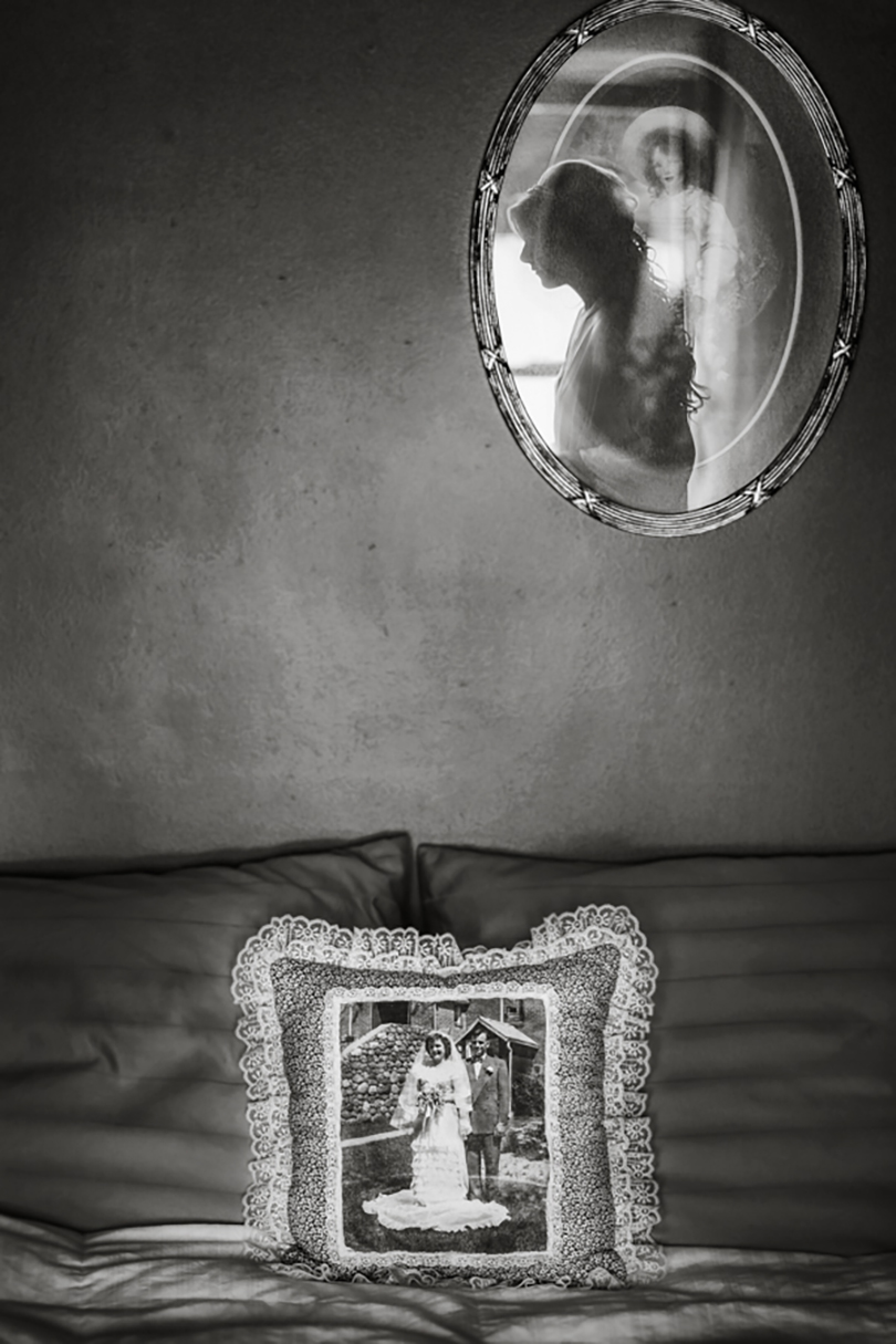 Bride reflected in mirror above vintage photo pillow of parents,  Amber Henry Photography, Michigan