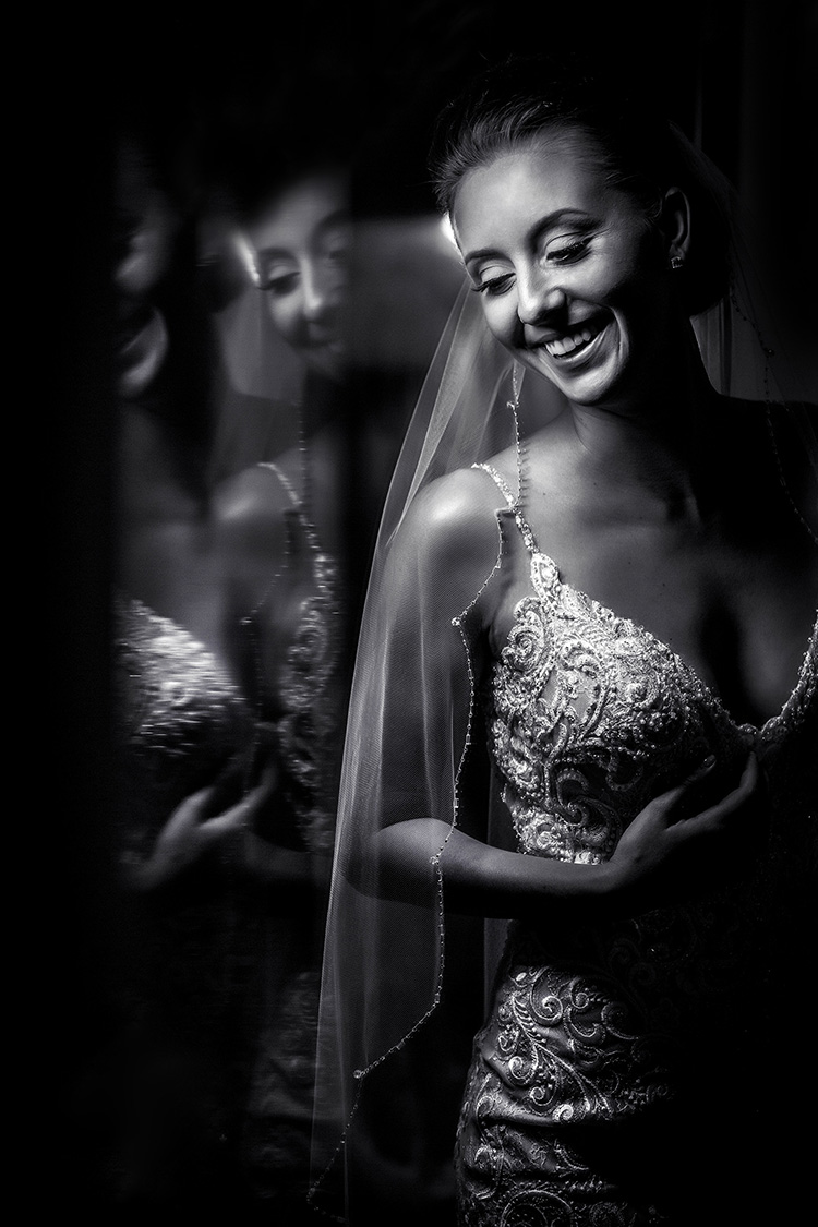 Laughing bride in beaded spaghetti strap gown reflected in mirror, photo by Amber Henry Photography, Michigan